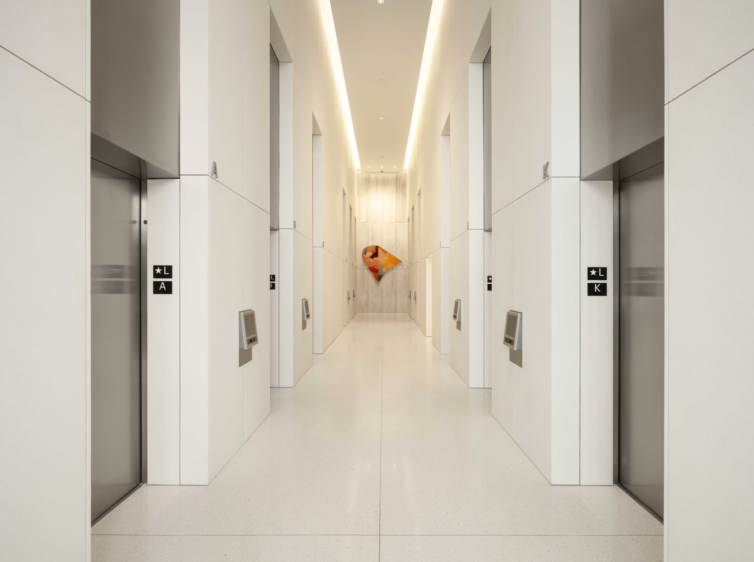 A hallway in an office building that has some elevators on either side of it and some white walls.