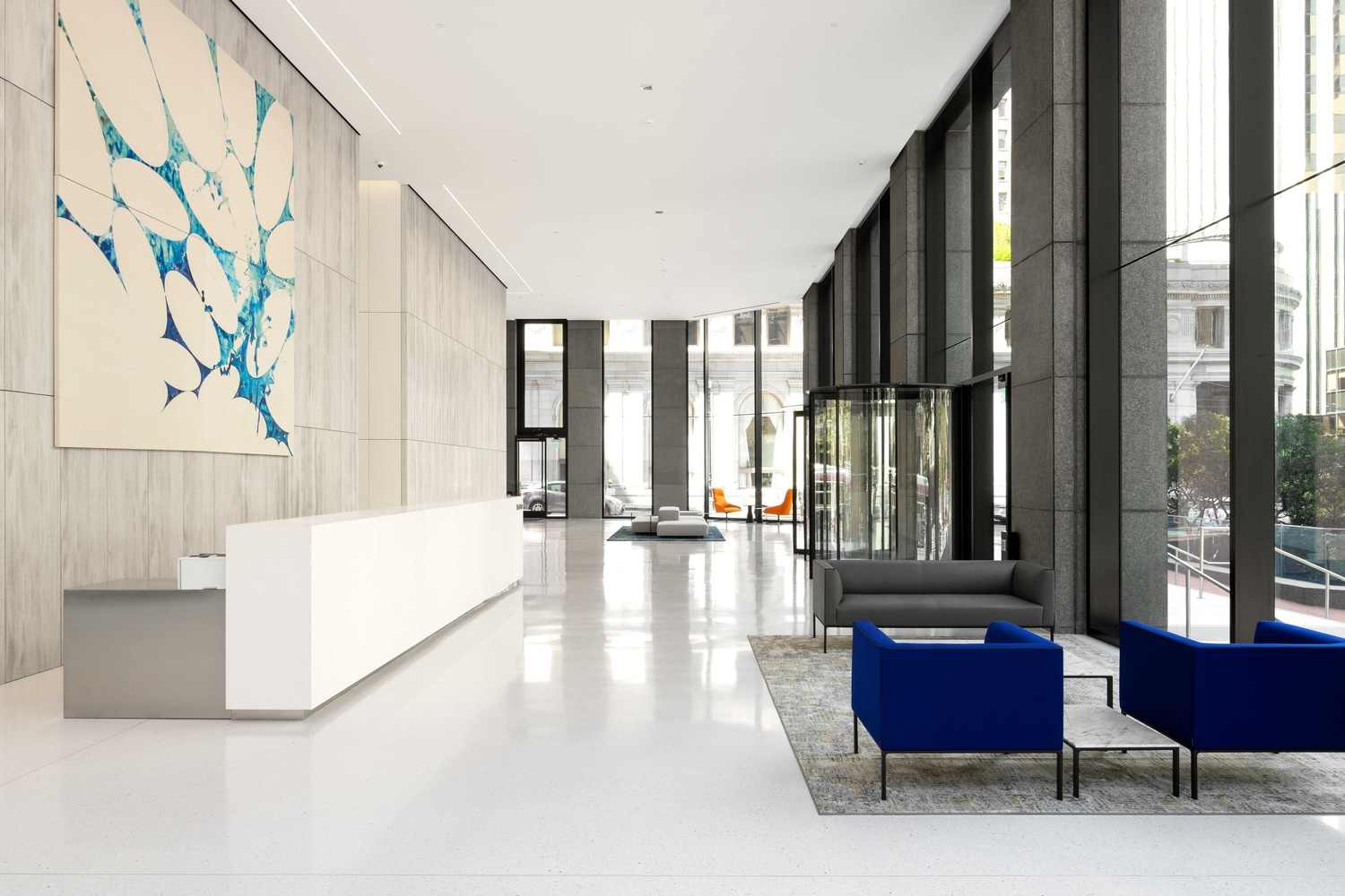 The inside of an office building at the lobby with chairs and a reception desk with art on the wall behind it.