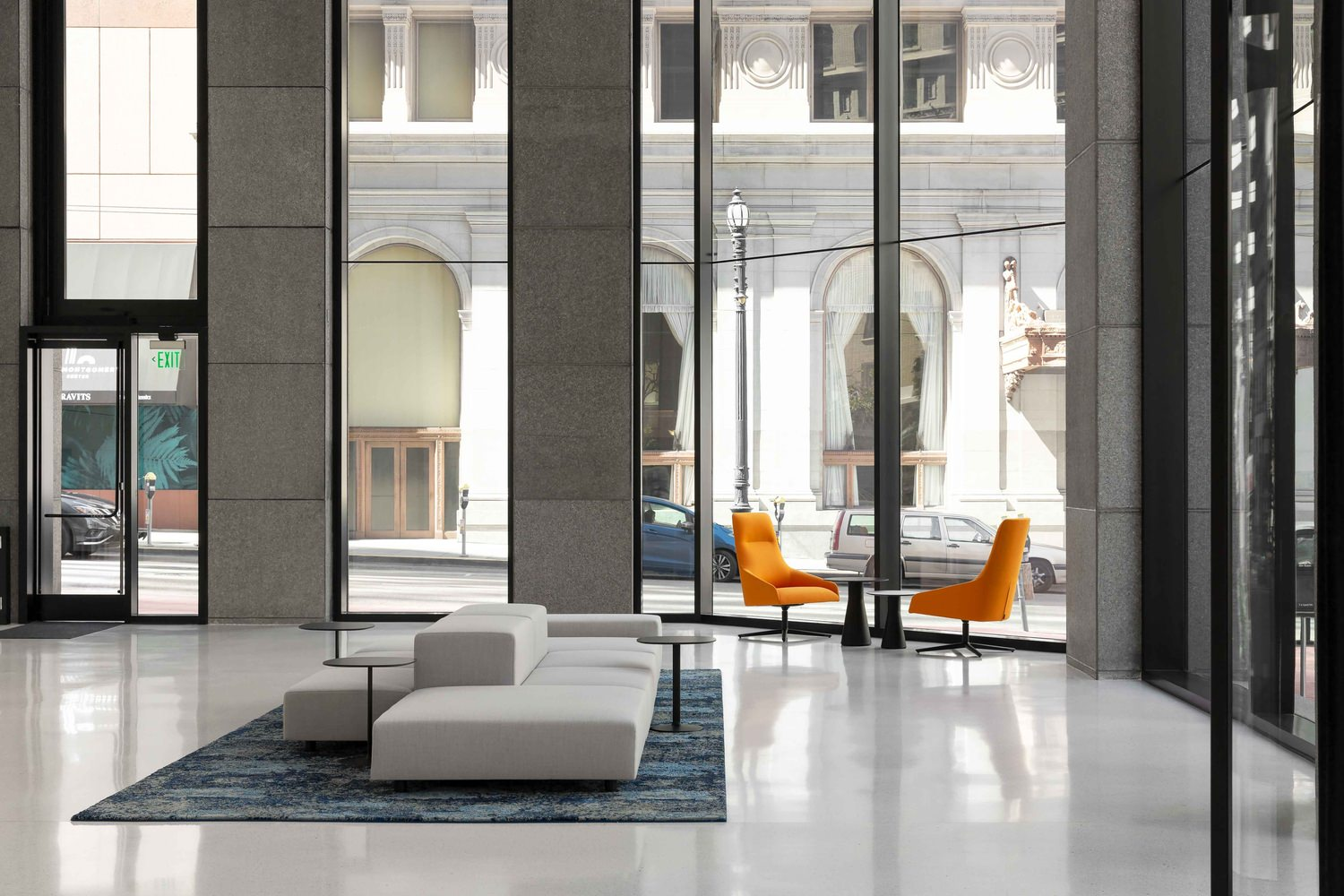 A lobby in a building that has a white couch and a table that has two orange chairs at it.
