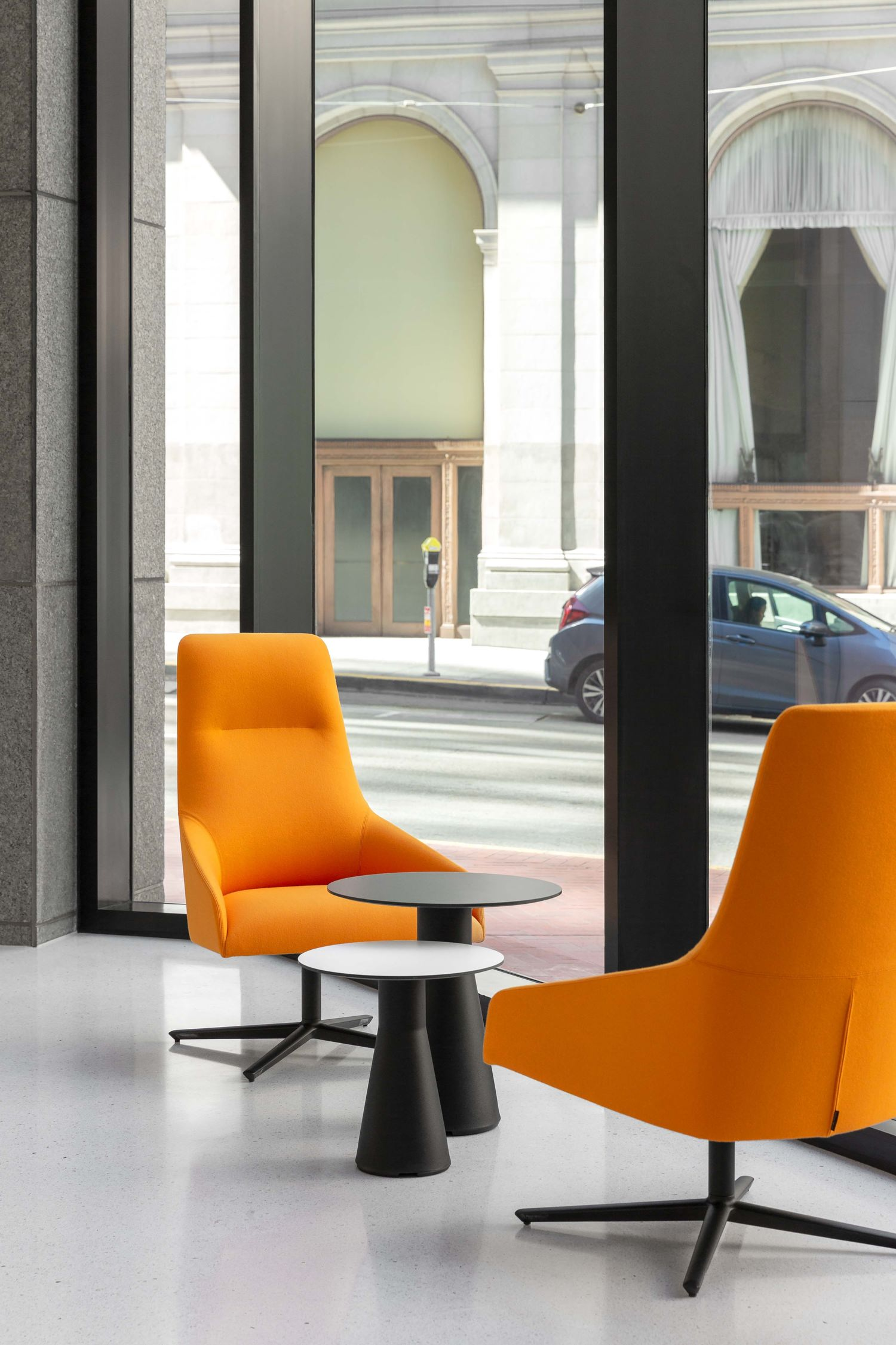 Two orange chairs that are sitting in a lobby around a couple of small tables on a white tile floor.
