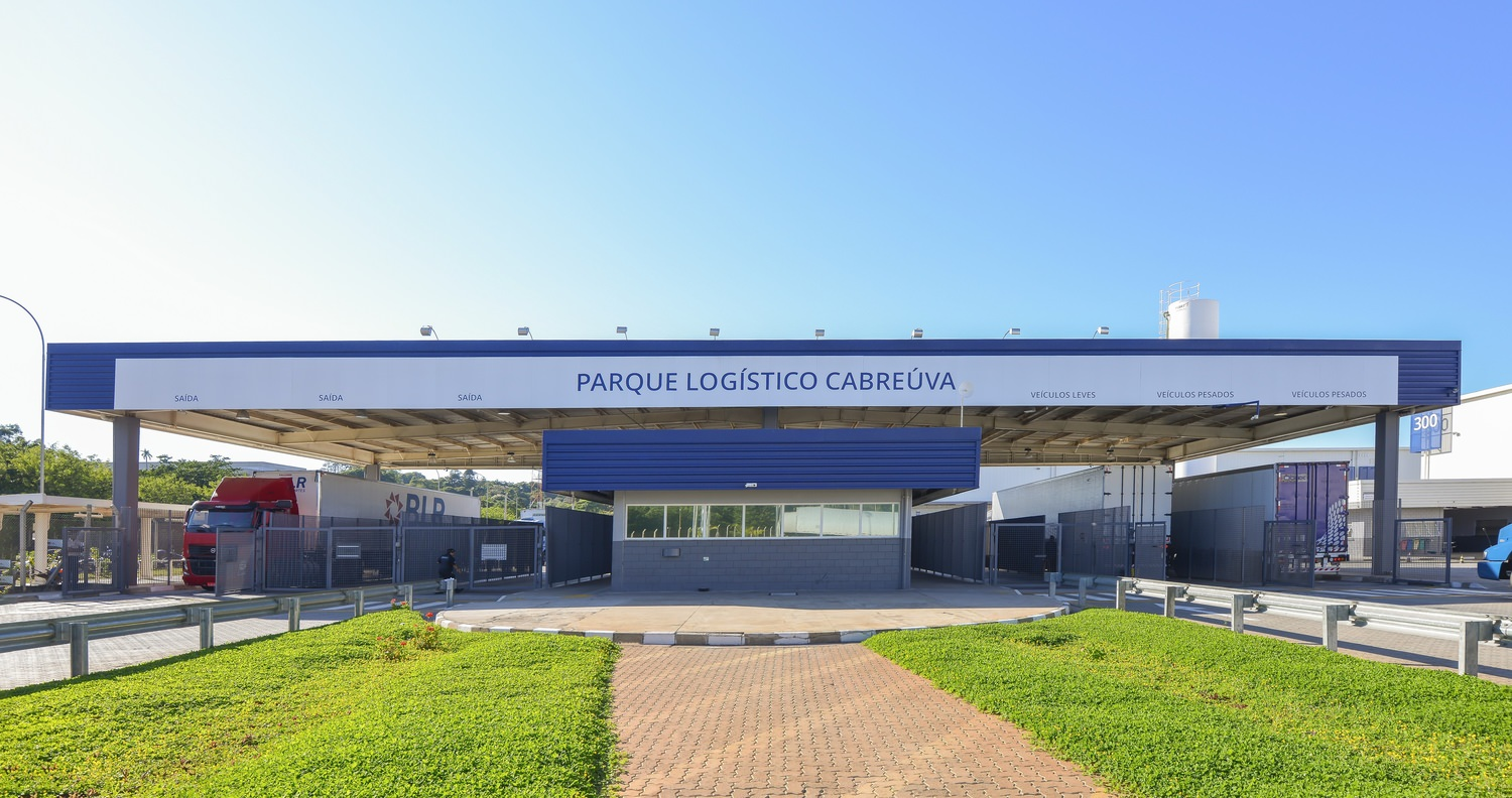 """Picture of a truck loading area with a sign that says """"PARQUE LOGISTICO CABREUVA"""""""