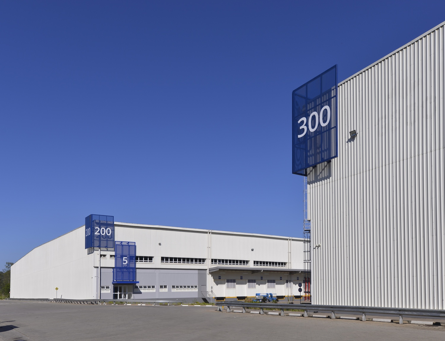 """Two large warehouses, one labeled """"300"""" and the other labeled """"200"""" with a 5 above a doorway."""