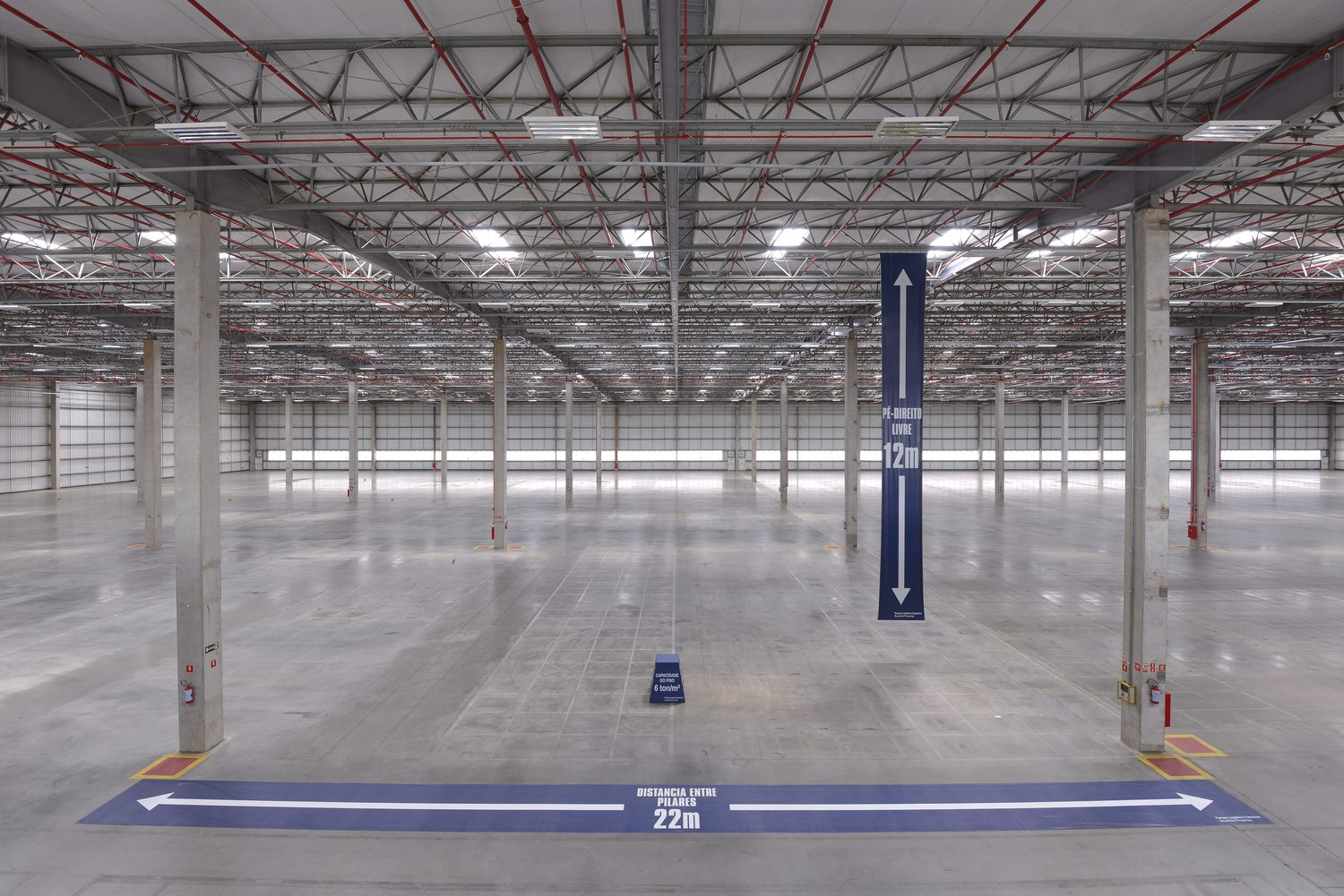 Interior of a parking area for trucks. There are signs signaling the space is 22m wide and 12m tall.