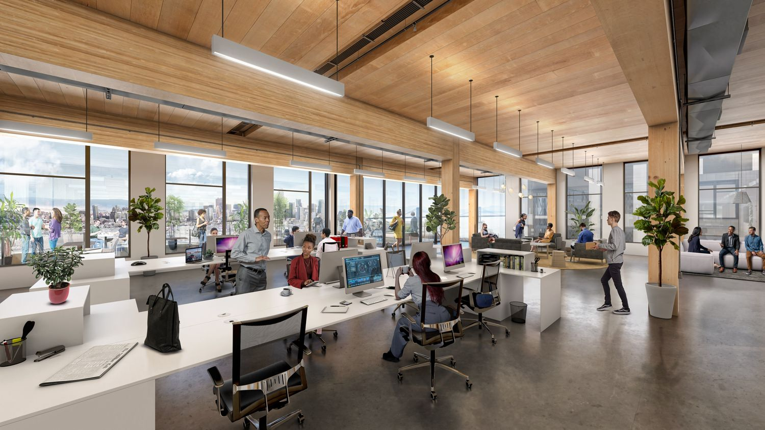 An open-concept office space with people working at shared desks.