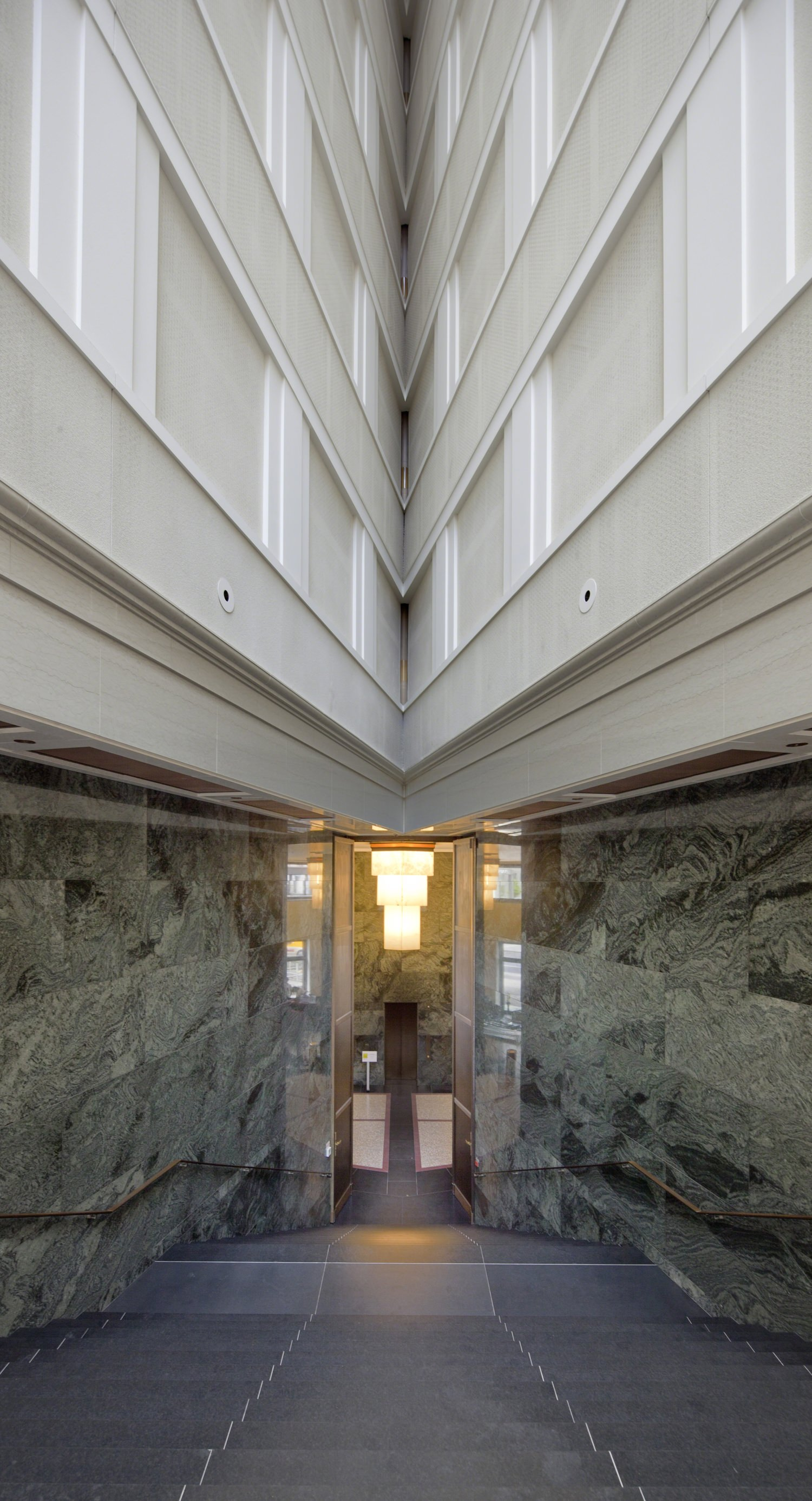 A glass door opens to the sidewalk in a stone room in a building with a white top.