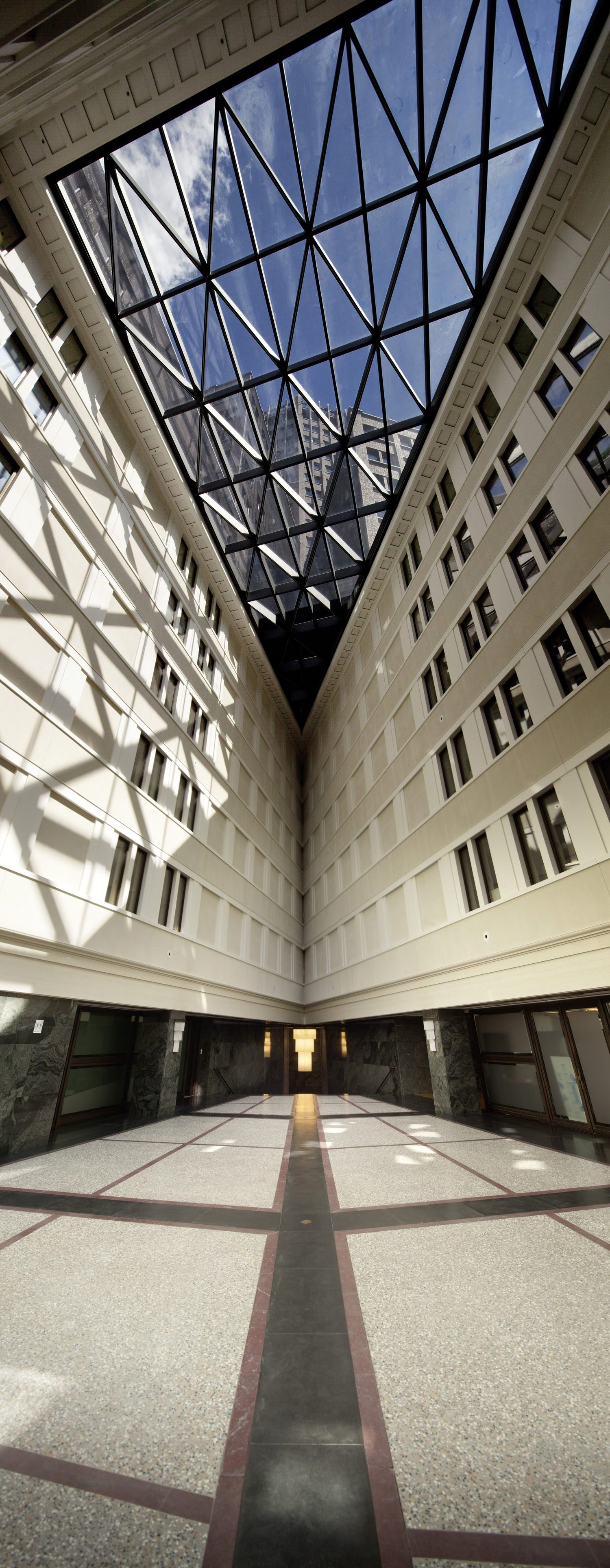A courtyard inside of a building that has a glass skylight on the top of it and windows.