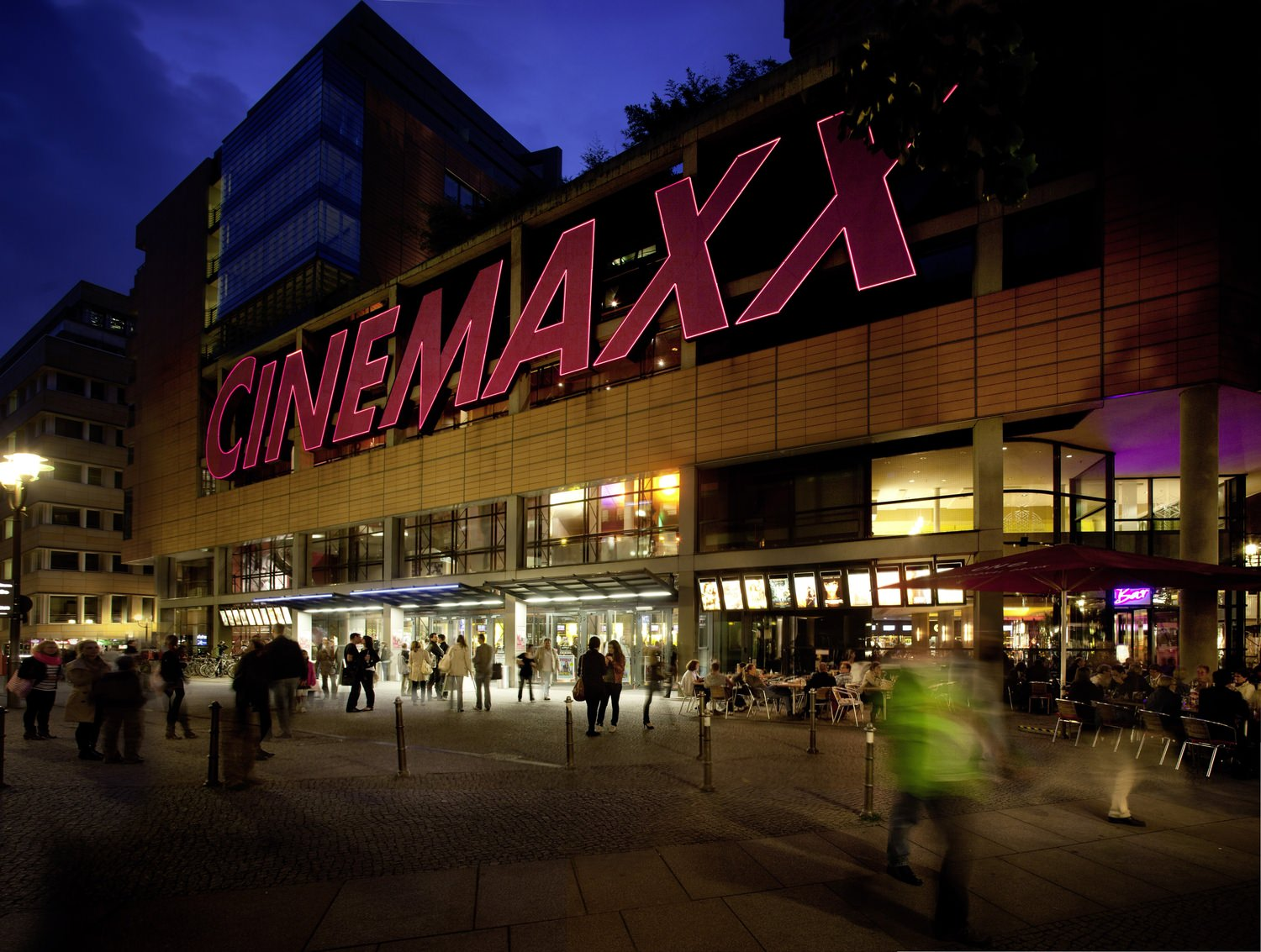 A movie theater that has up a sign that says Cinemaxx on it and there are people walking up to it.