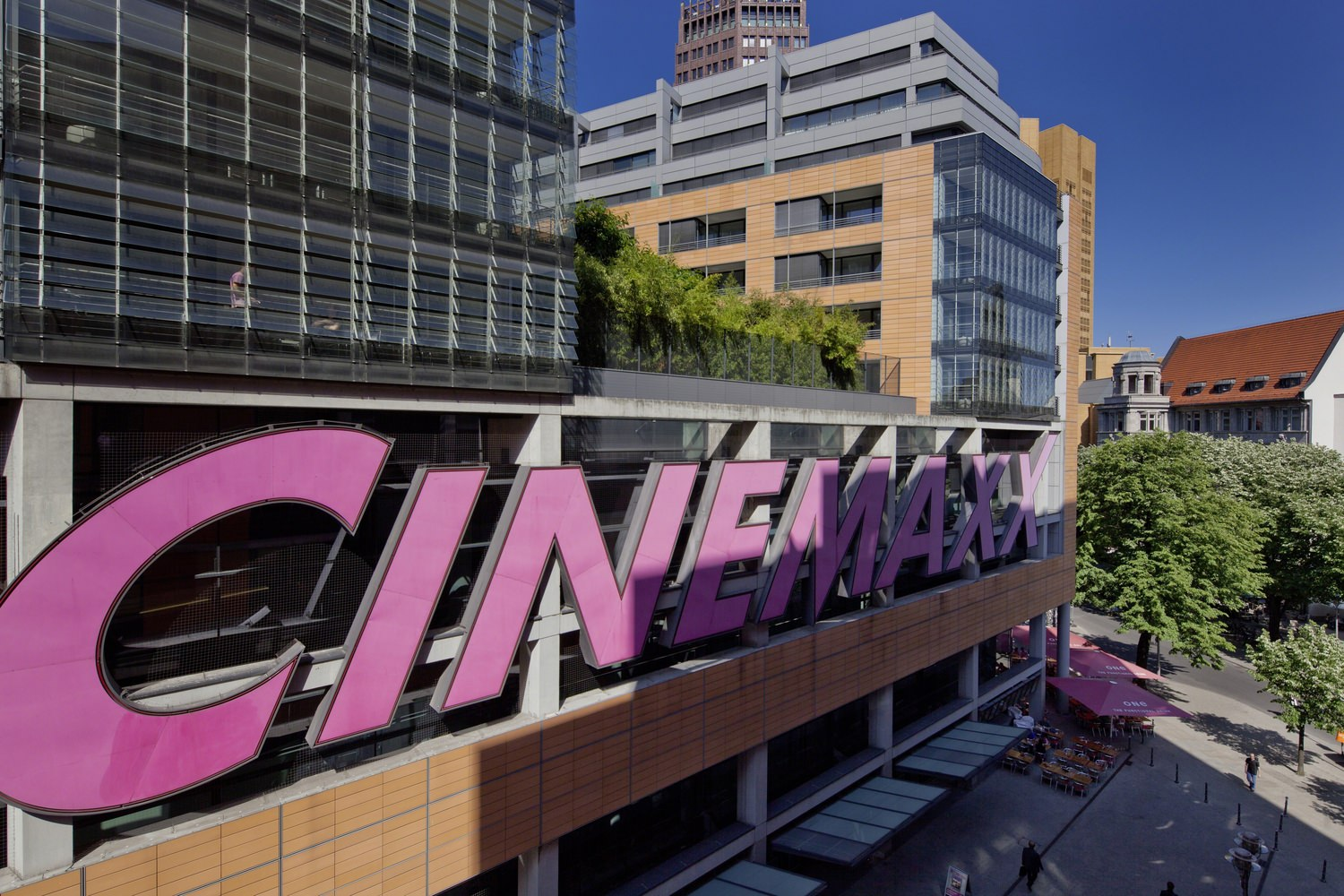 A movie theater that has a pink sign that says Cinemaxx on it and there are people walking in front of it.