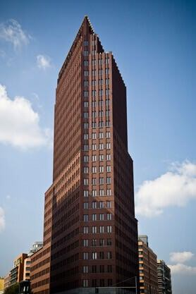 A tall brown skyscraper that has rows of buildings behind it within the busy city.