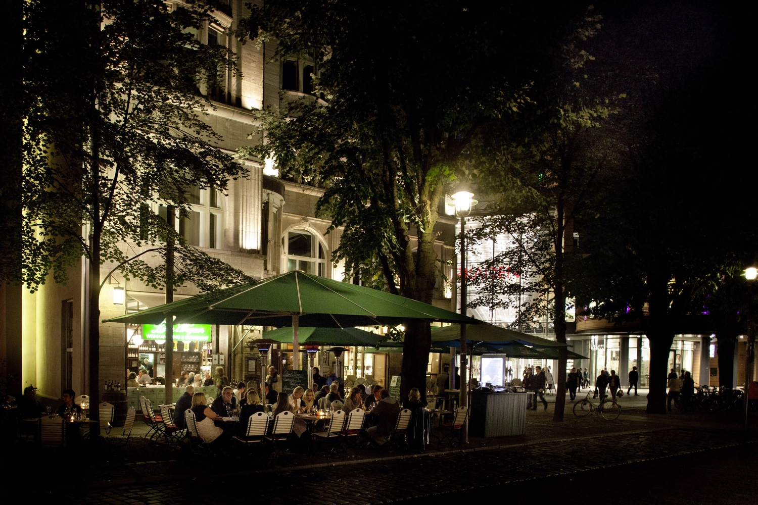 A crowd of people eating at the outdoor patio of a restaurant at night in the city.