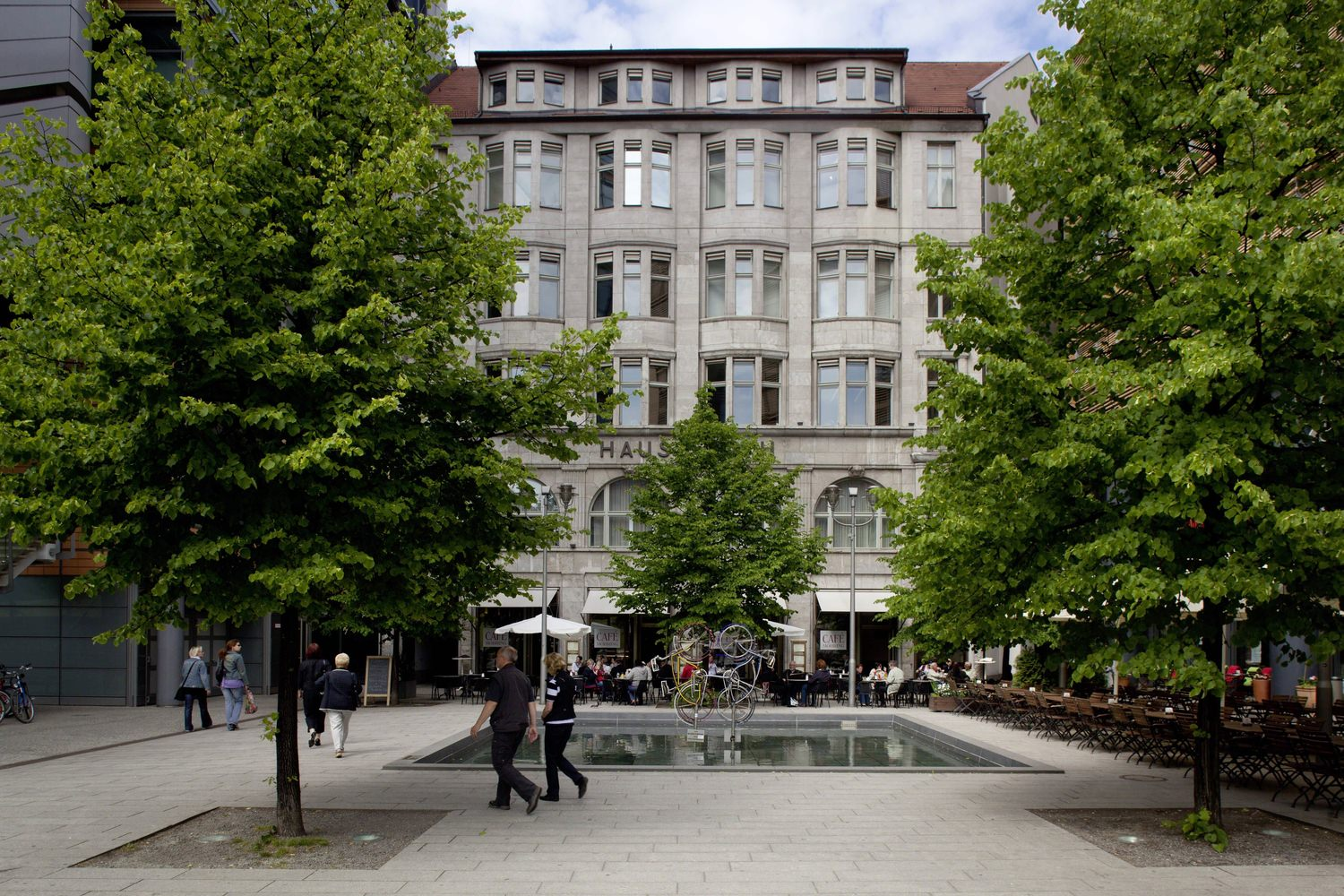 People walking along the outdoor area of a building that has a fountain and rows of trees.