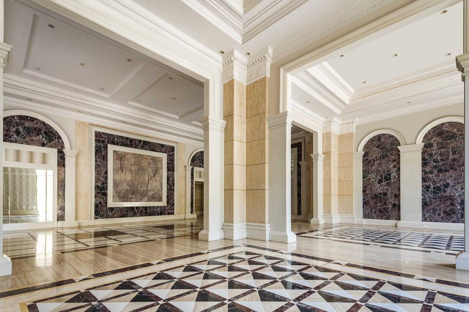 A large lobby that has walls with marbles and floors full of tiles along the area.