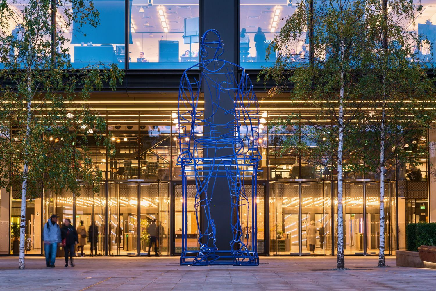 Entrance to a lit lobby during the evening. A large blue wire sculpture of a man sitting sits in the center of the frame.