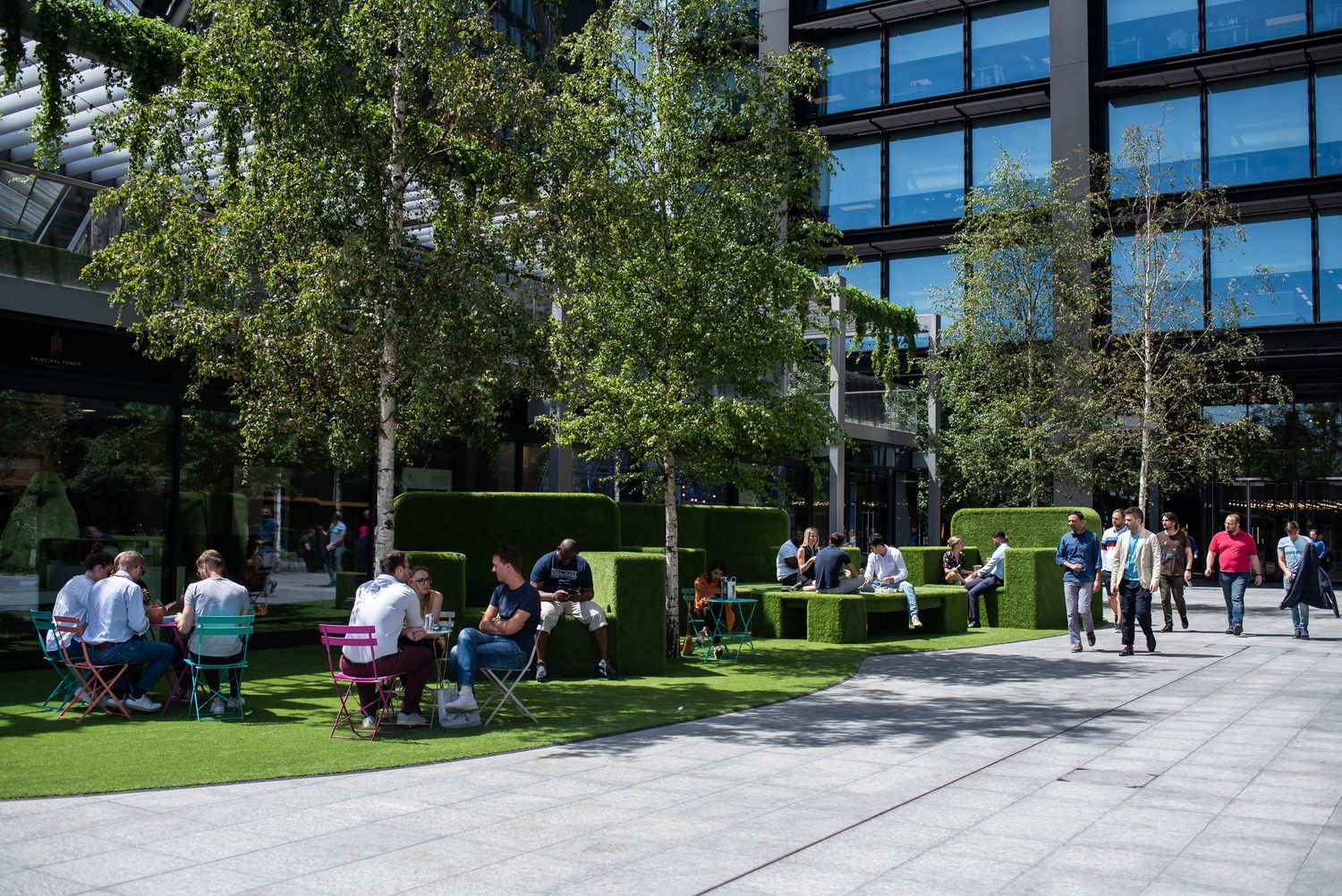A group of people that are sitting at tables in a grassy area in front of a building under some trees for shade.