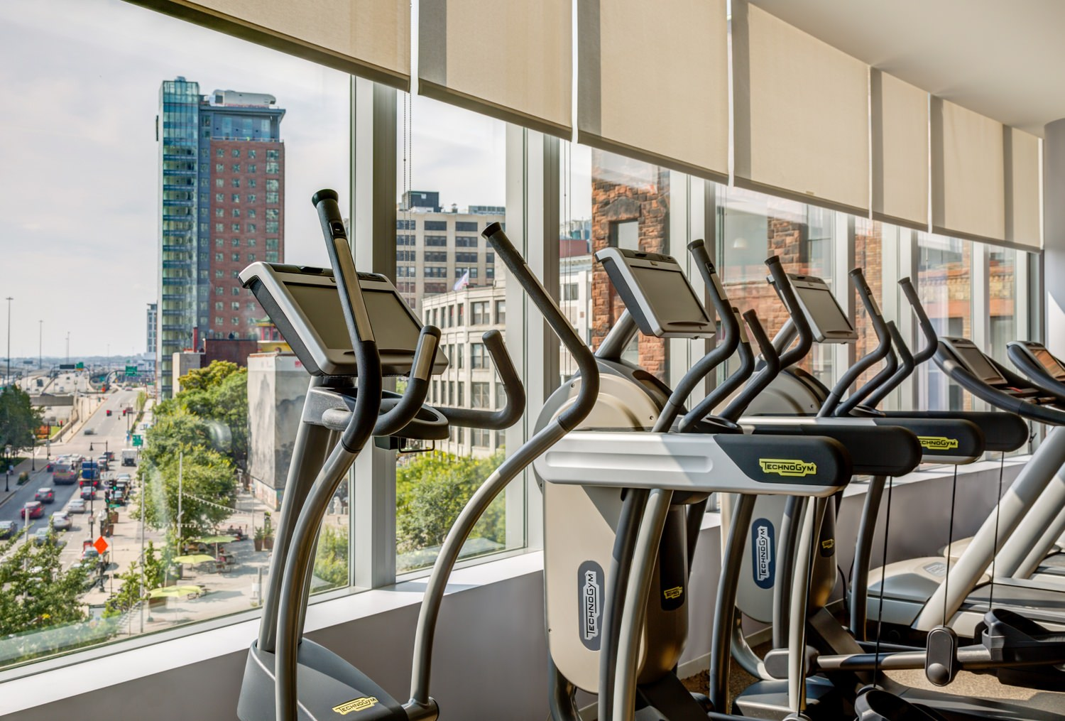 A gym in a building that has elliptical machines and treadmills that are looking out the windows down to the road.
