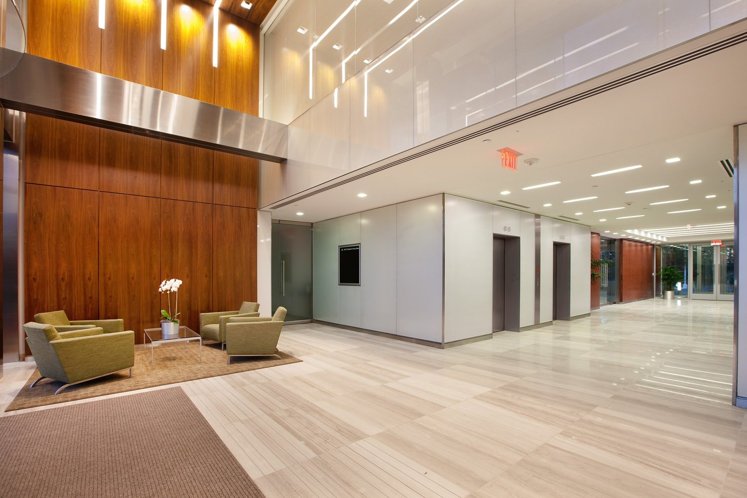 A large lobby of a building that has green couches and wooden panels along the walls.