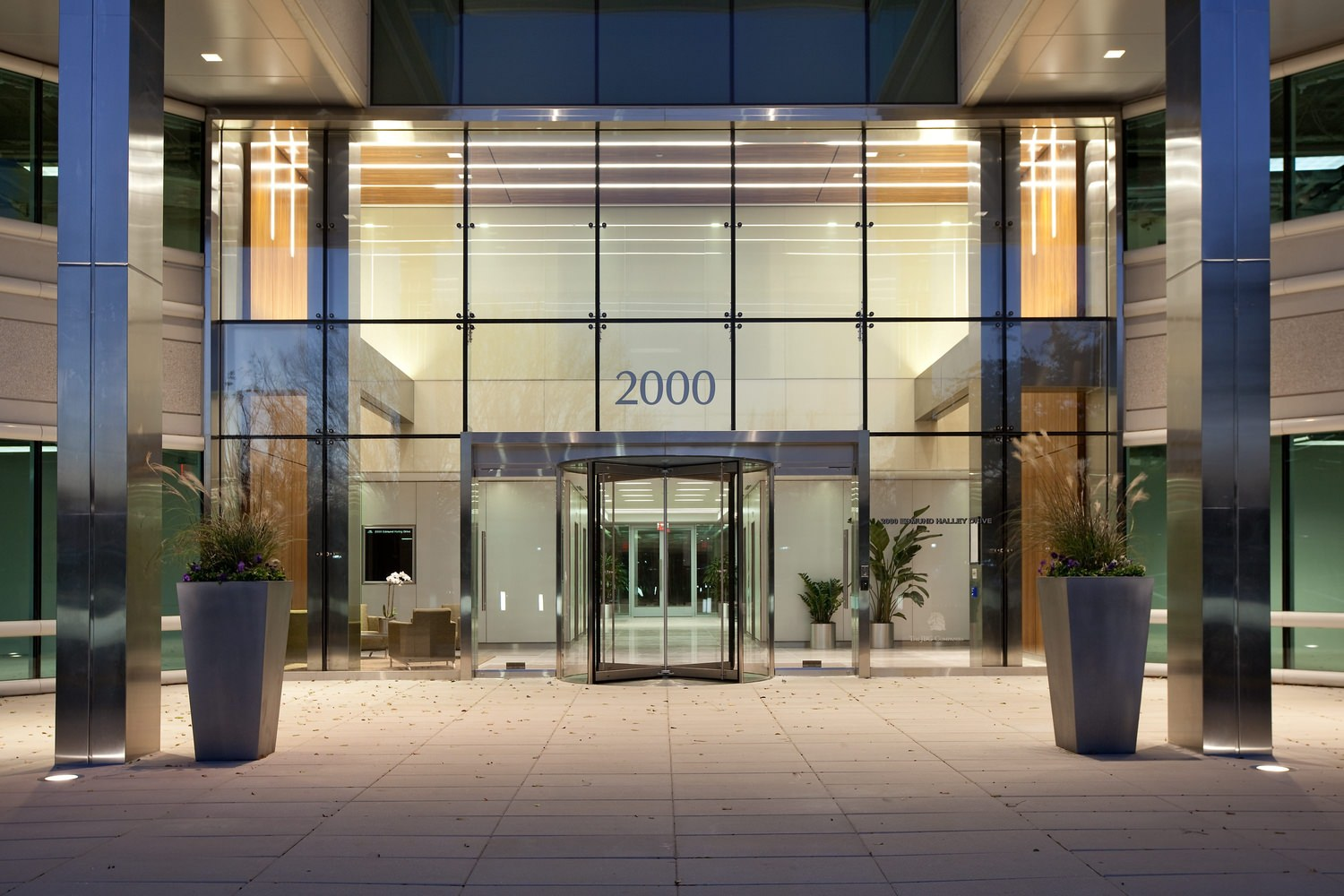 The front of a large building that has the address sign of 2000 and a wall full of glass windows.