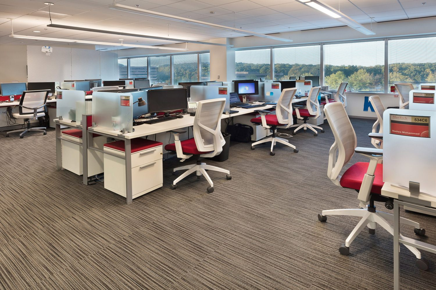An office where there are desks, computers, and chairs at each one of the desks.