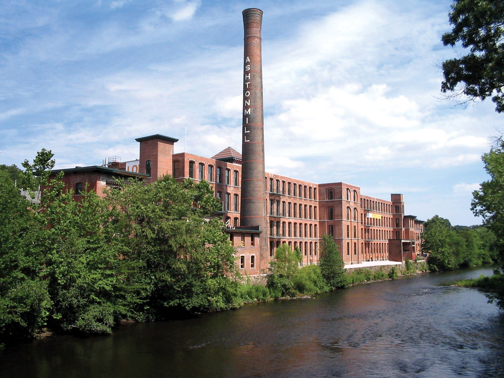 A large brick building with a tower that is next to a row of trees and a river.