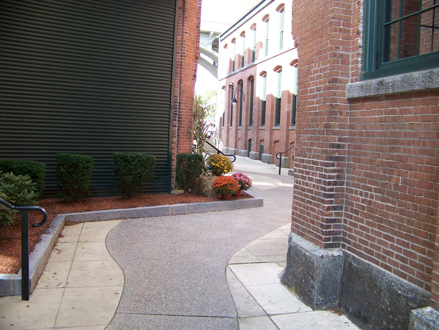 Secluded sidewalk between two brick buildings.