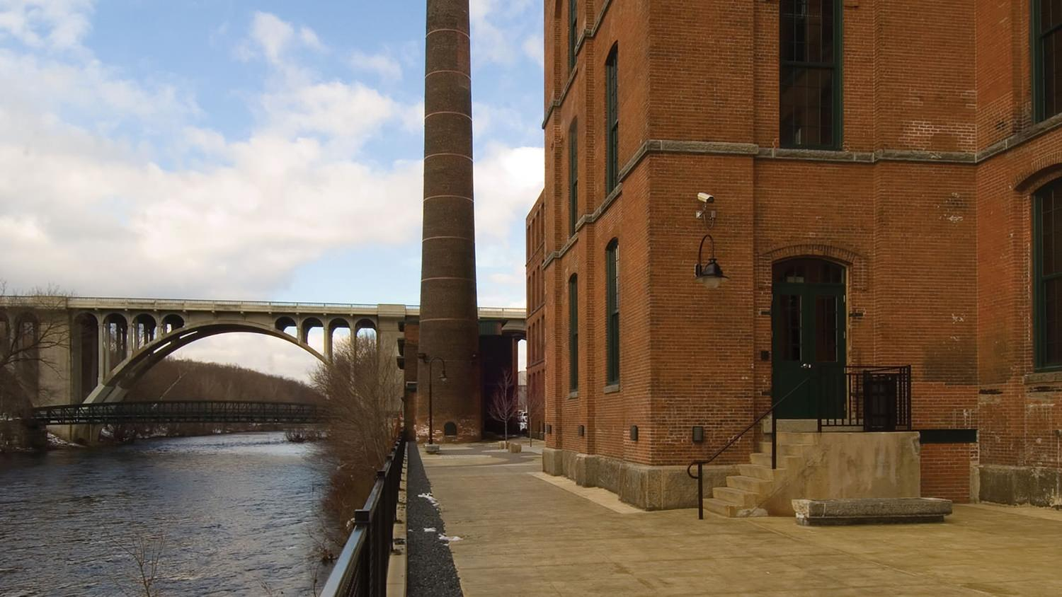 A large brown brick building with a tower that is next to a river and a bridge.