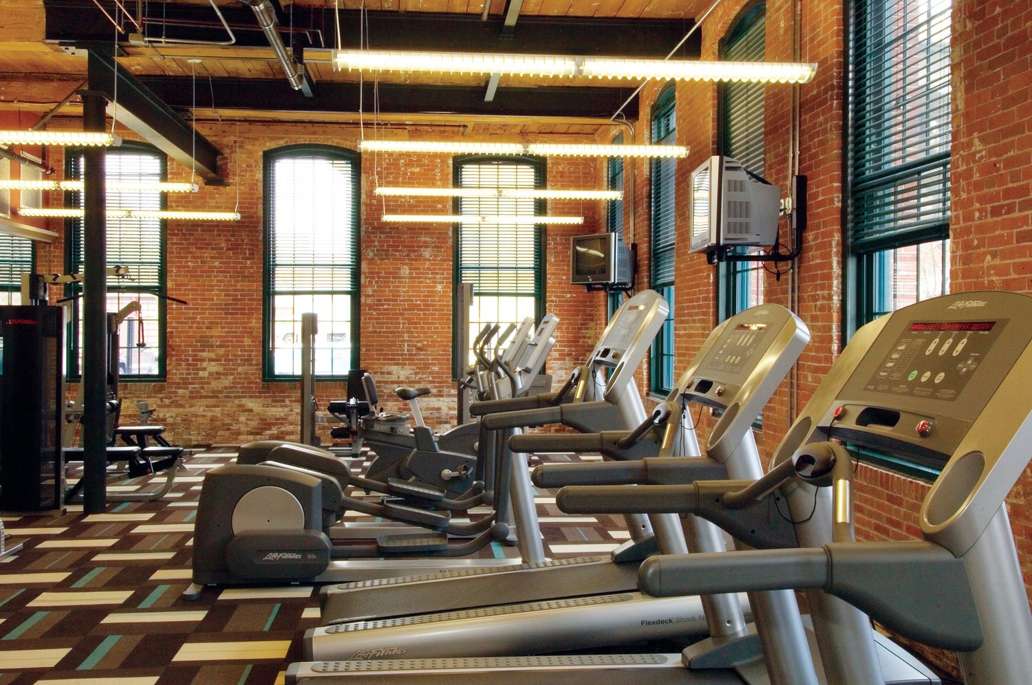 A row of treadmills in a gym with other exercise equipment inside a brick building.