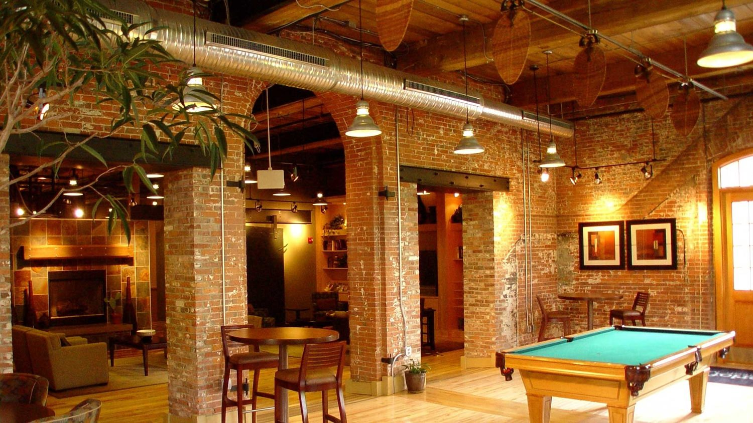 A game room inside of a brick building that has a billiard table and other furnitures.