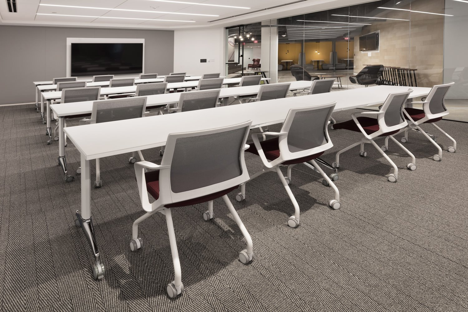 Rows of white tables with chairs inside of a room full of computers and other furniture.