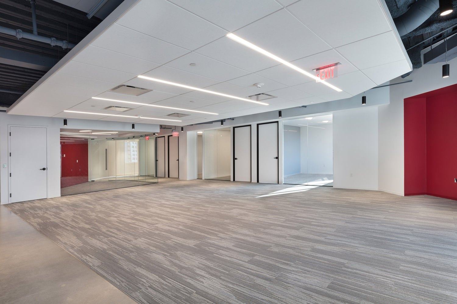A large room that is empty and has a white drop ceiling in it and wood floors for it.