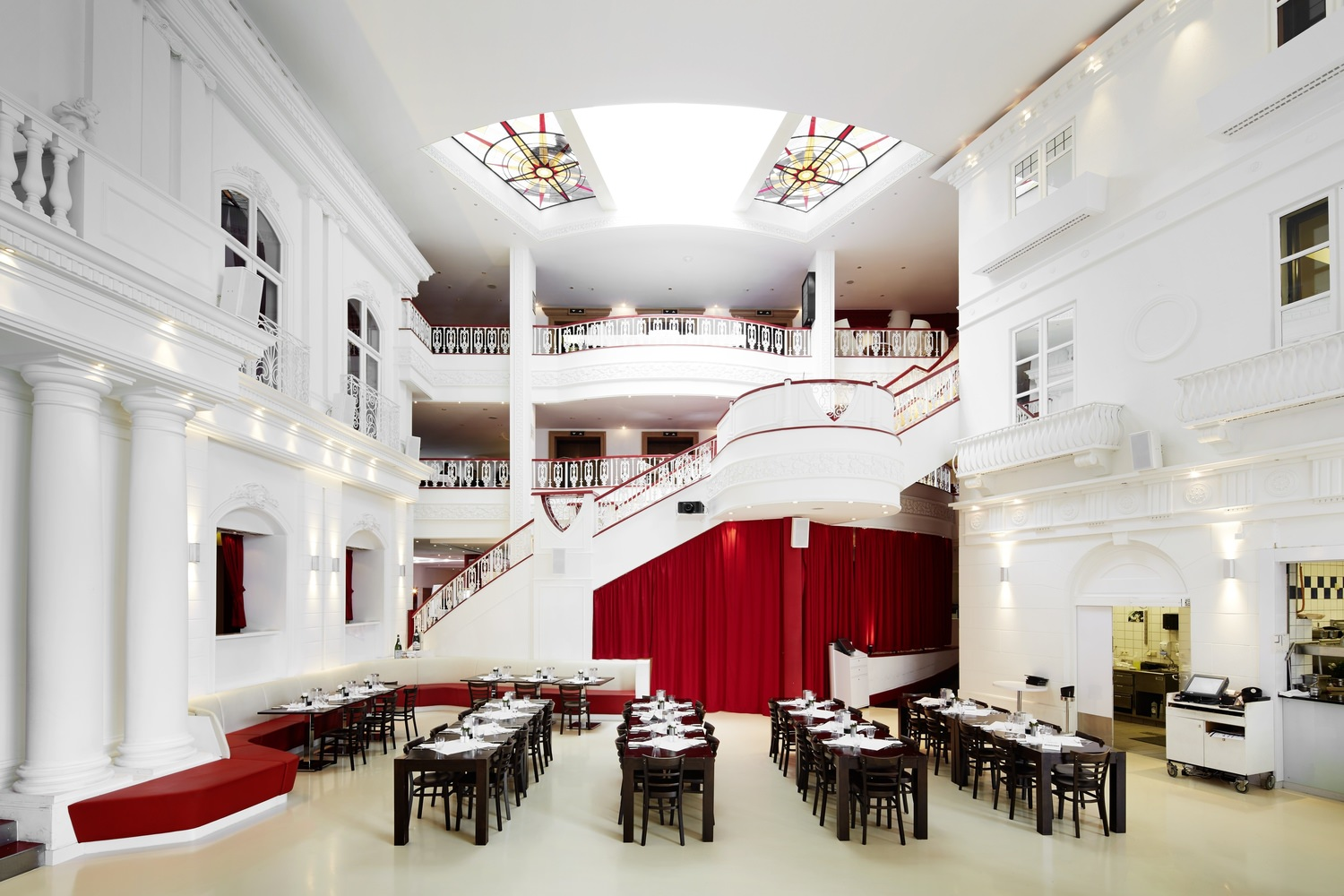 A large indoor lobby full of tables and chairs with a flight of stairs in the background.
