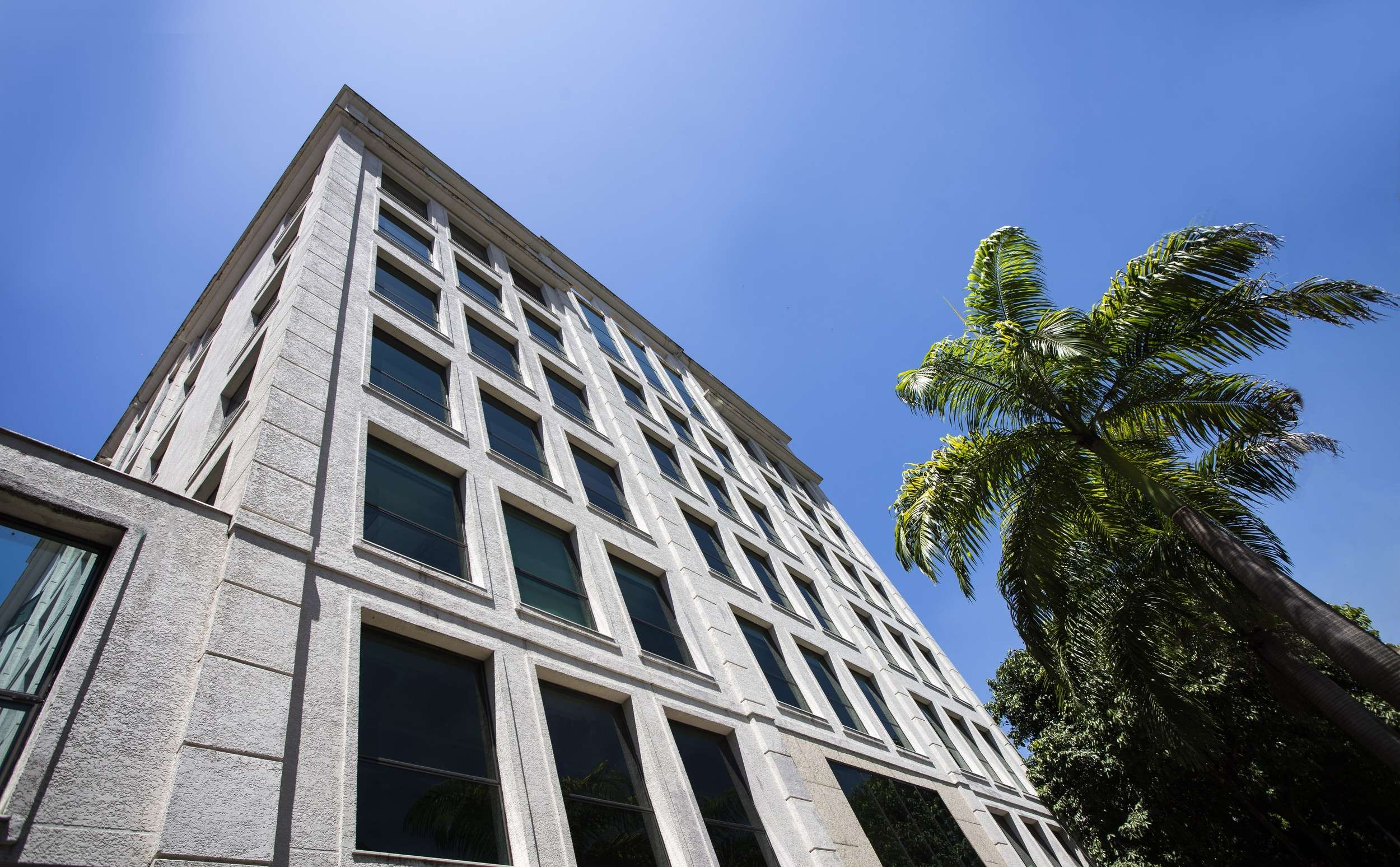 A six story tall building that is made out of concrete and block with windows looking out a palm tre