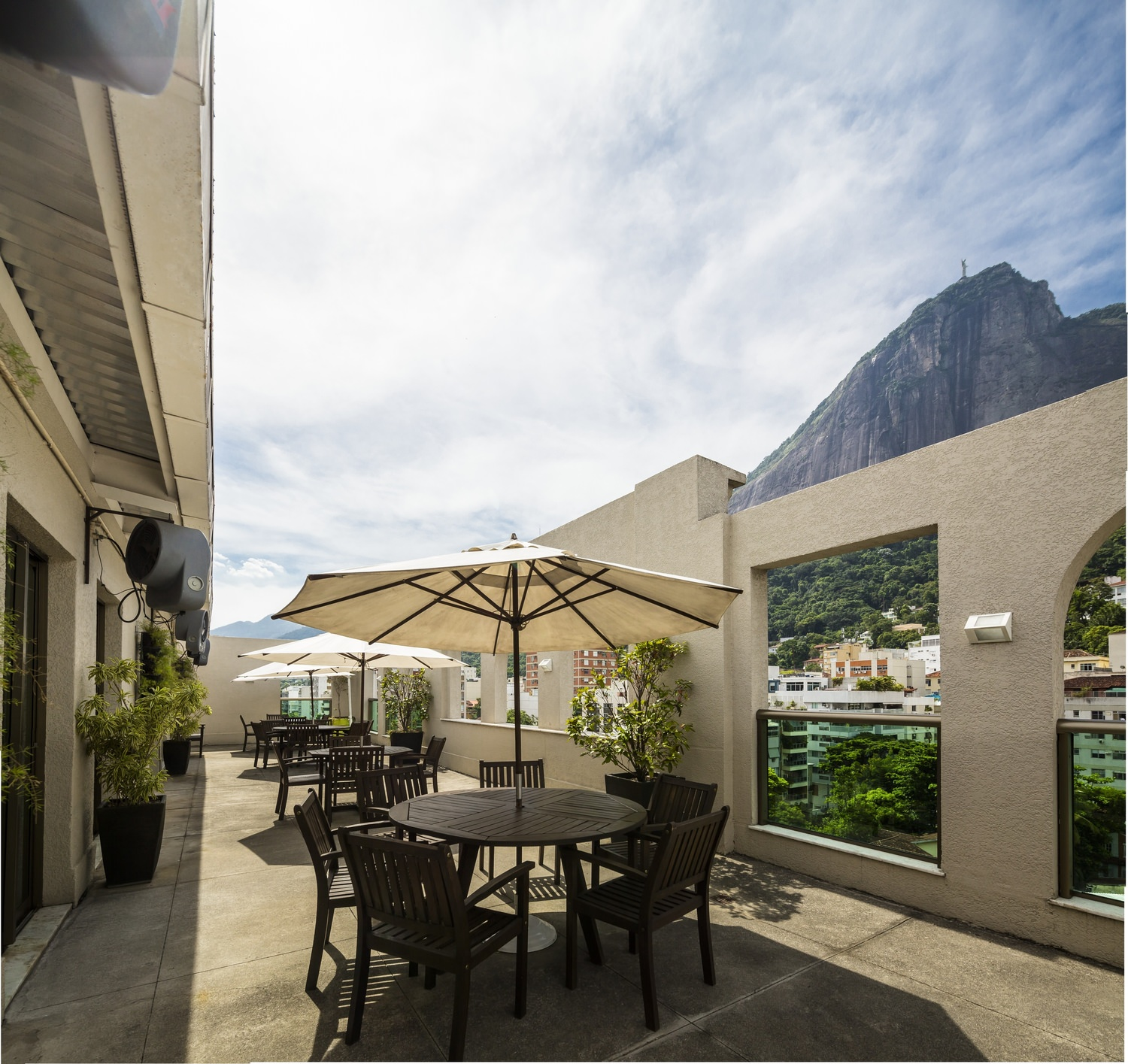 A patio that has some tables with umbrellas and chairs around them outside of a restaurant.