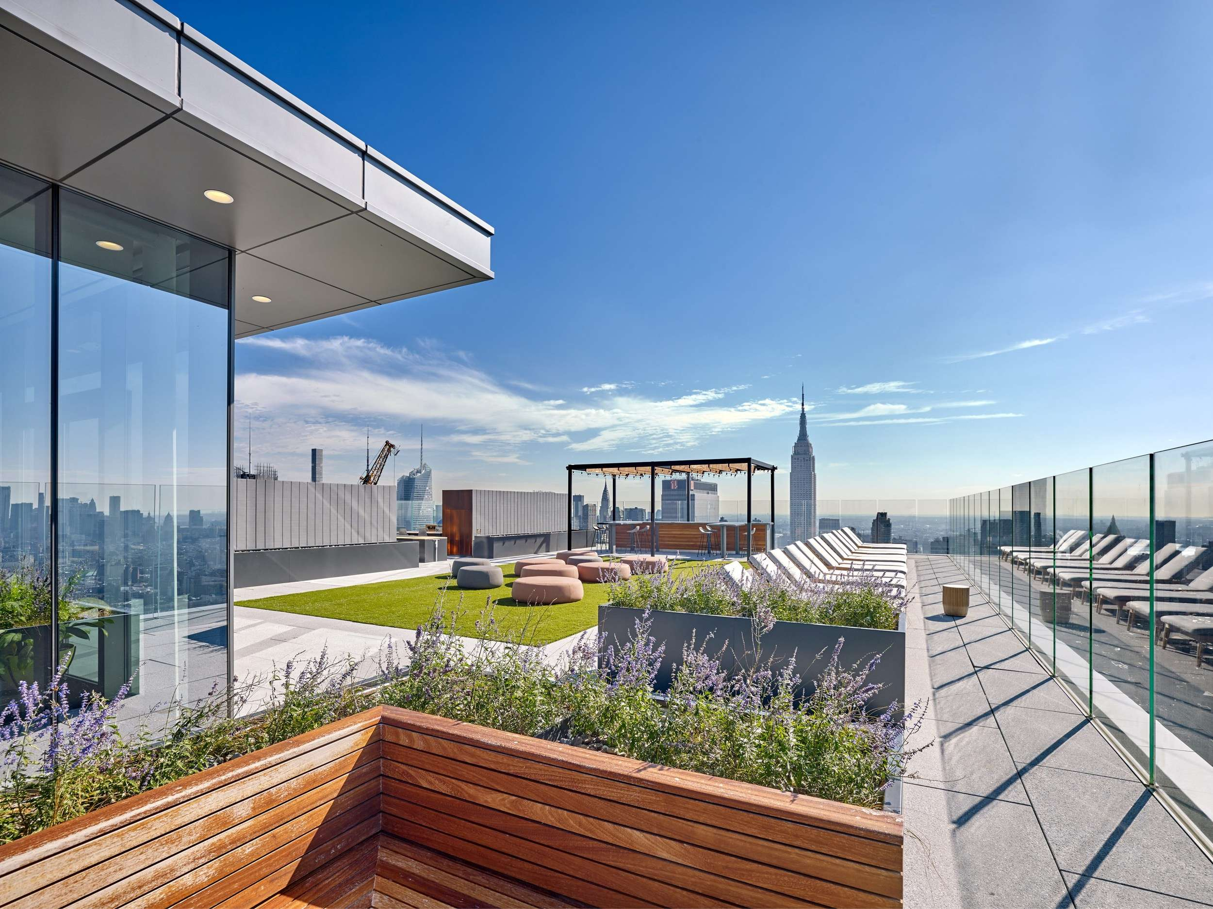 An outdoor sitting area that is located on the roof of a building with grass and plants all around i