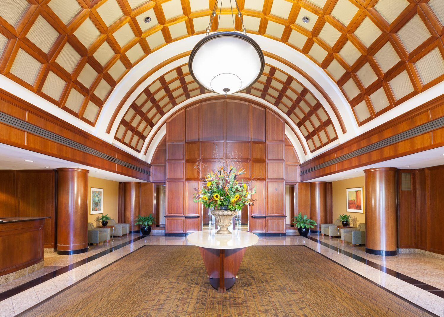 A wood paneled lobby with a ceiling that curves.