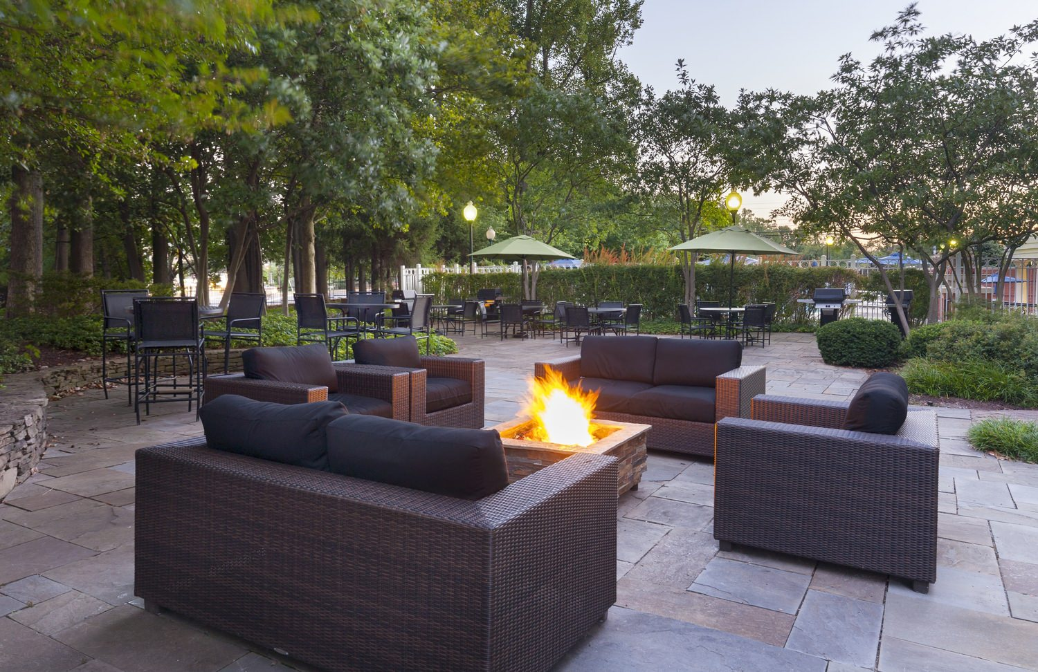 Outdoor chairs and couches circle a fire pit on a patio.