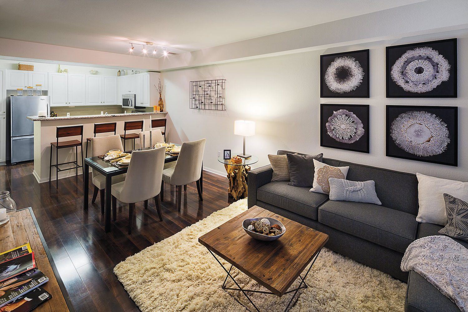 A kitchen and living room area that is full of furniture like sofas and tables.