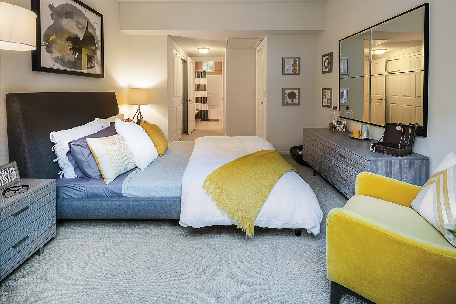 A bedroom that has a bed with sheets on it and a large mirror that is on the wall across form it.
