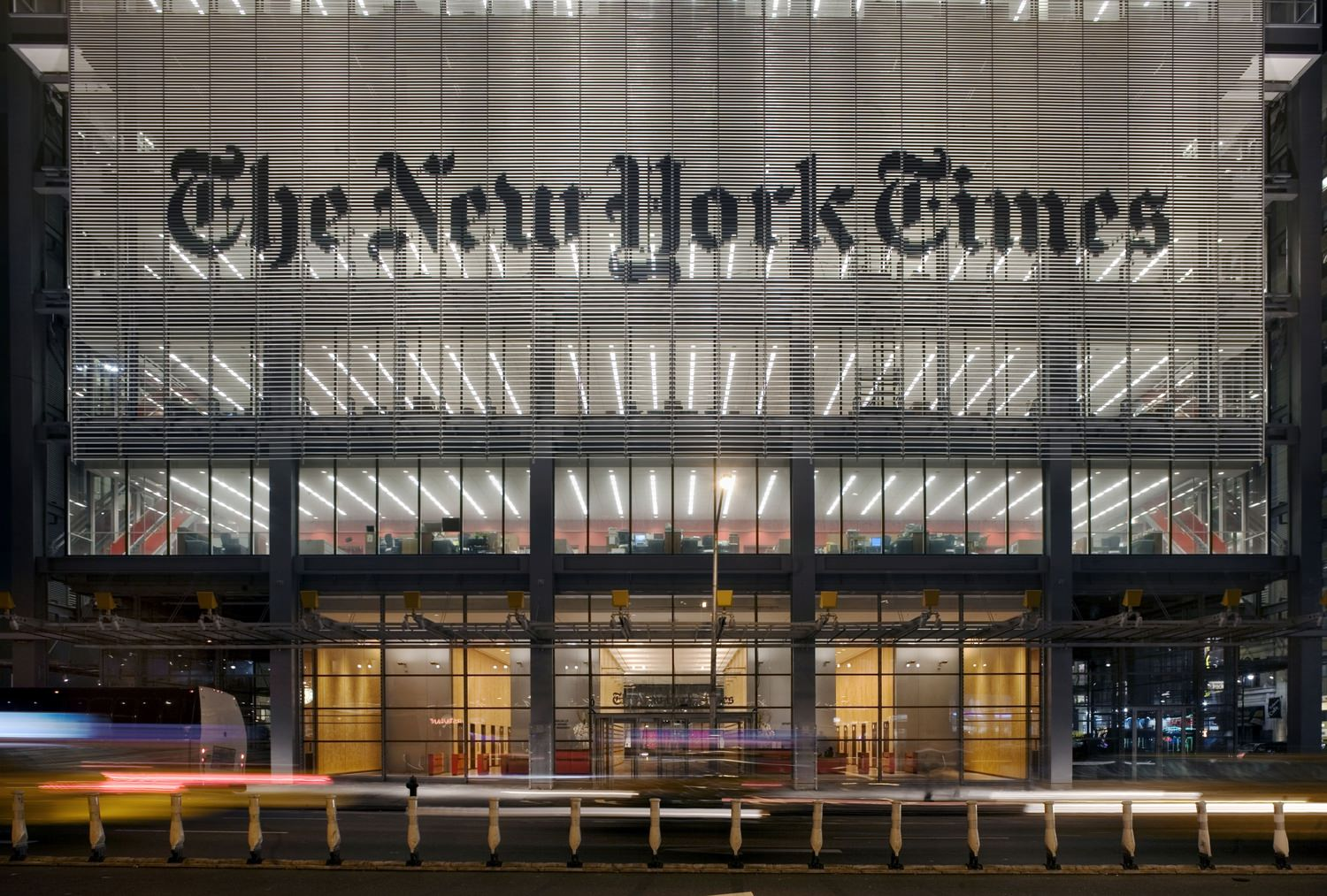 Exterior street view of the building entrance with large sign that says The New York Times.