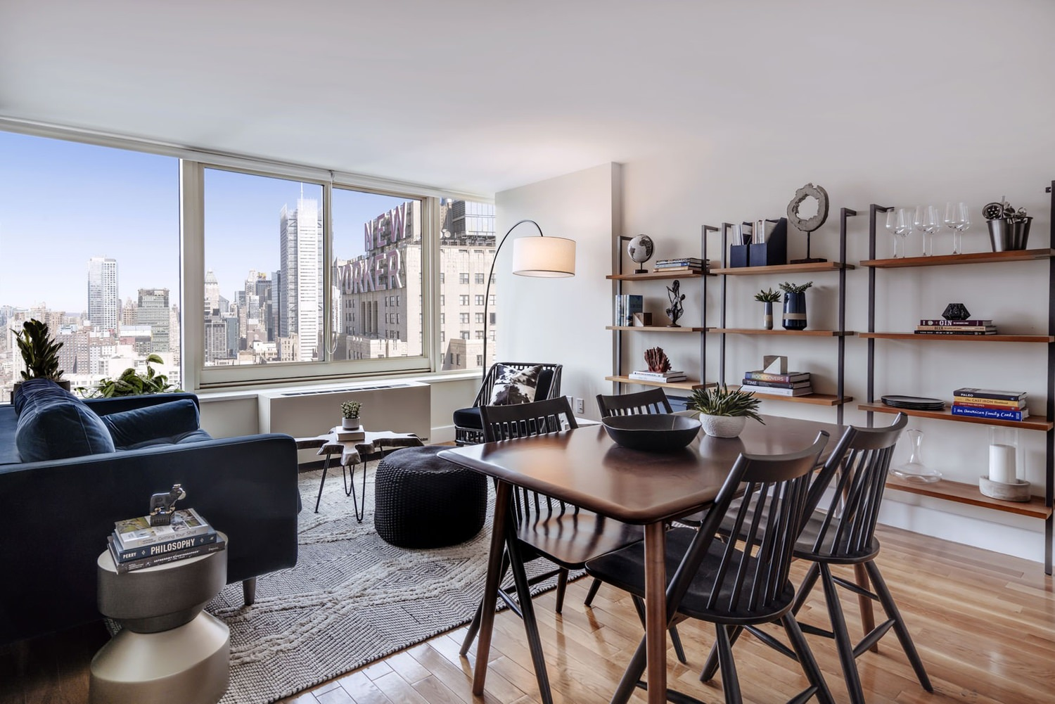 Dining and living room area of an apartment that has a view of the city skyline.