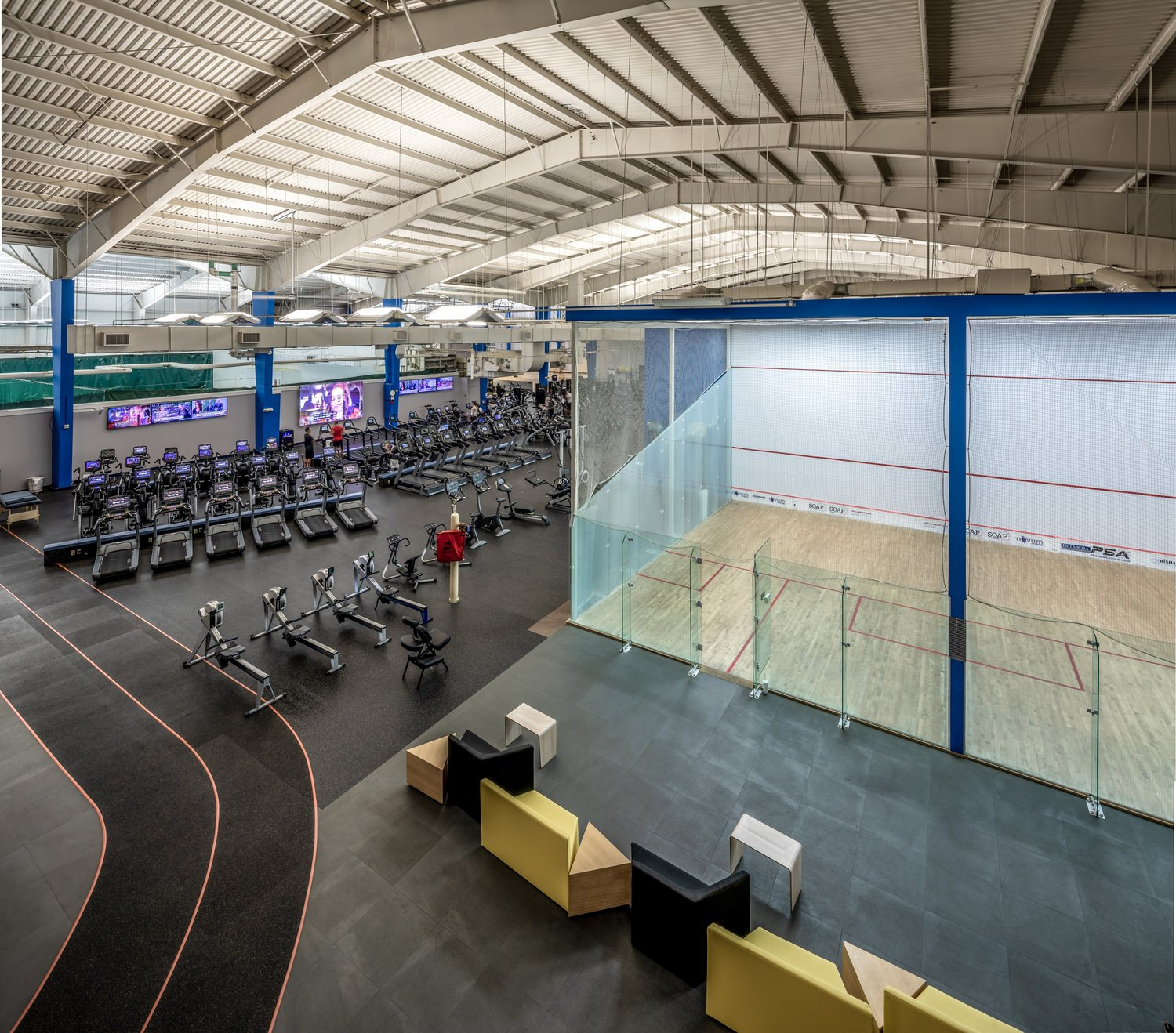 A large indoor gym that is full of furniture and exercise equipment lining the floor.