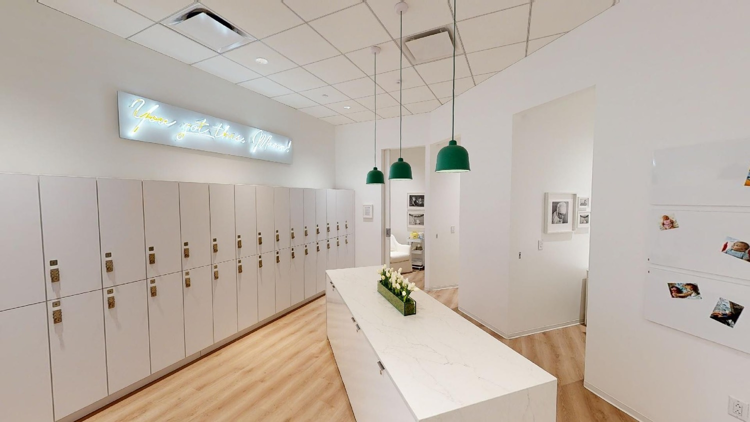 A room full of white lockers and and other furniture with a floor made of wooden panels.