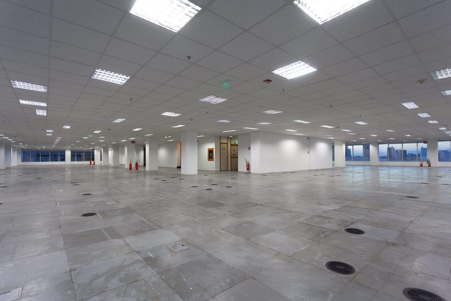 Large empty room that is full of white panels on the ceiling and grey tiles on the floor.
