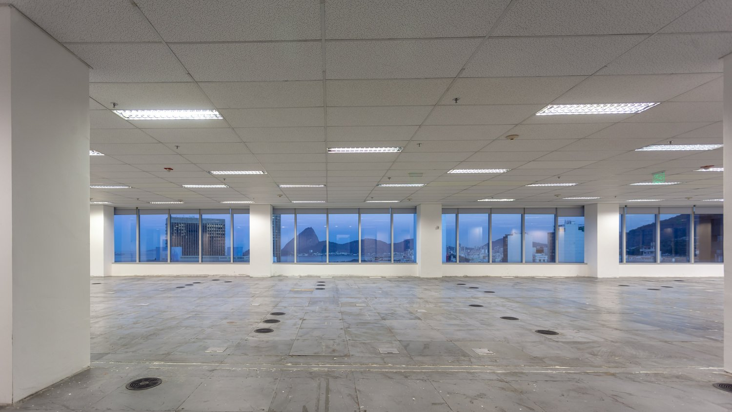 Large empty room with tiled floors and large glass windows that show a view of the vity in the background.