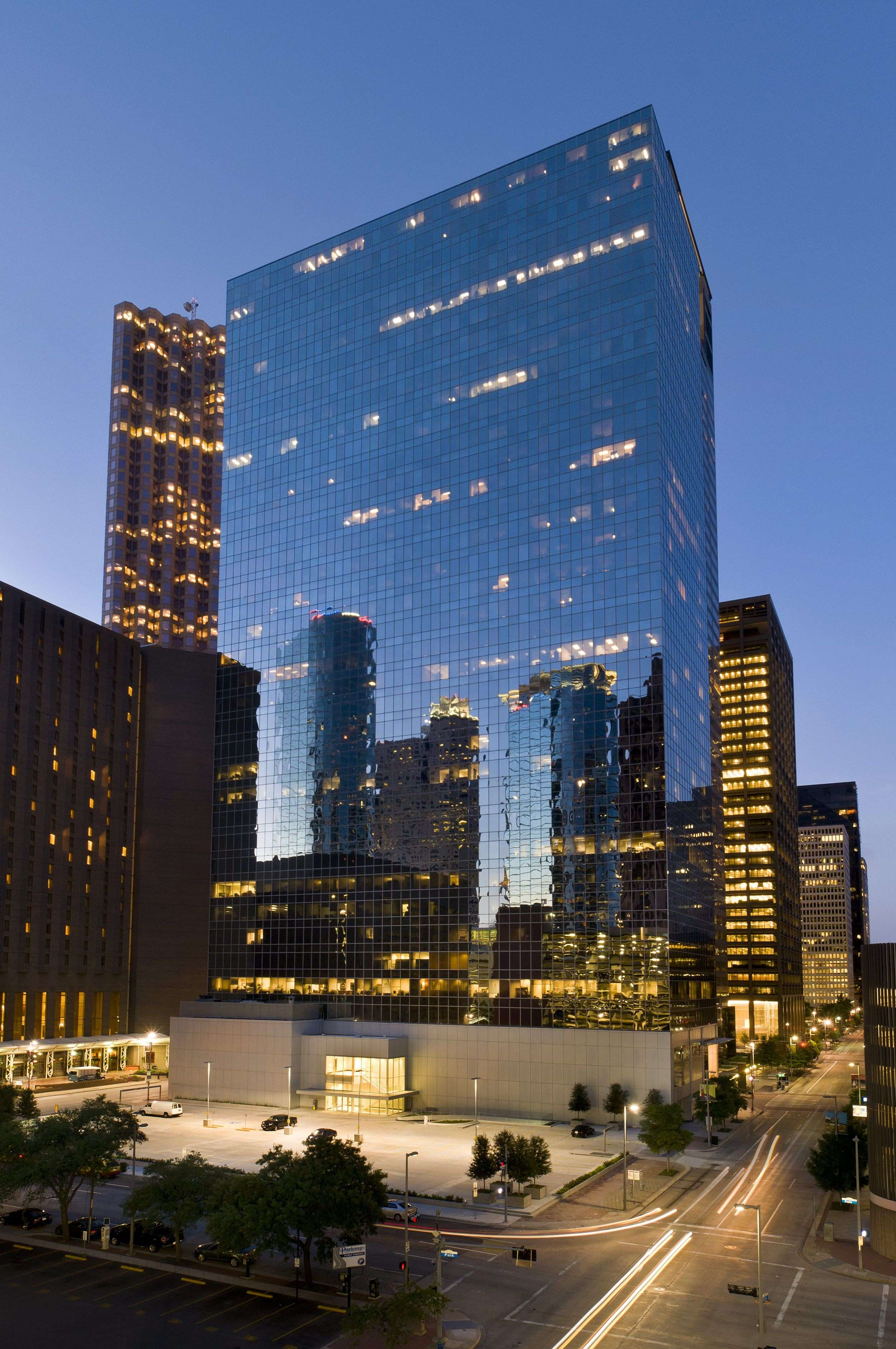 A skyscraper large building with full of glass windows built in the outdoor some distance away from