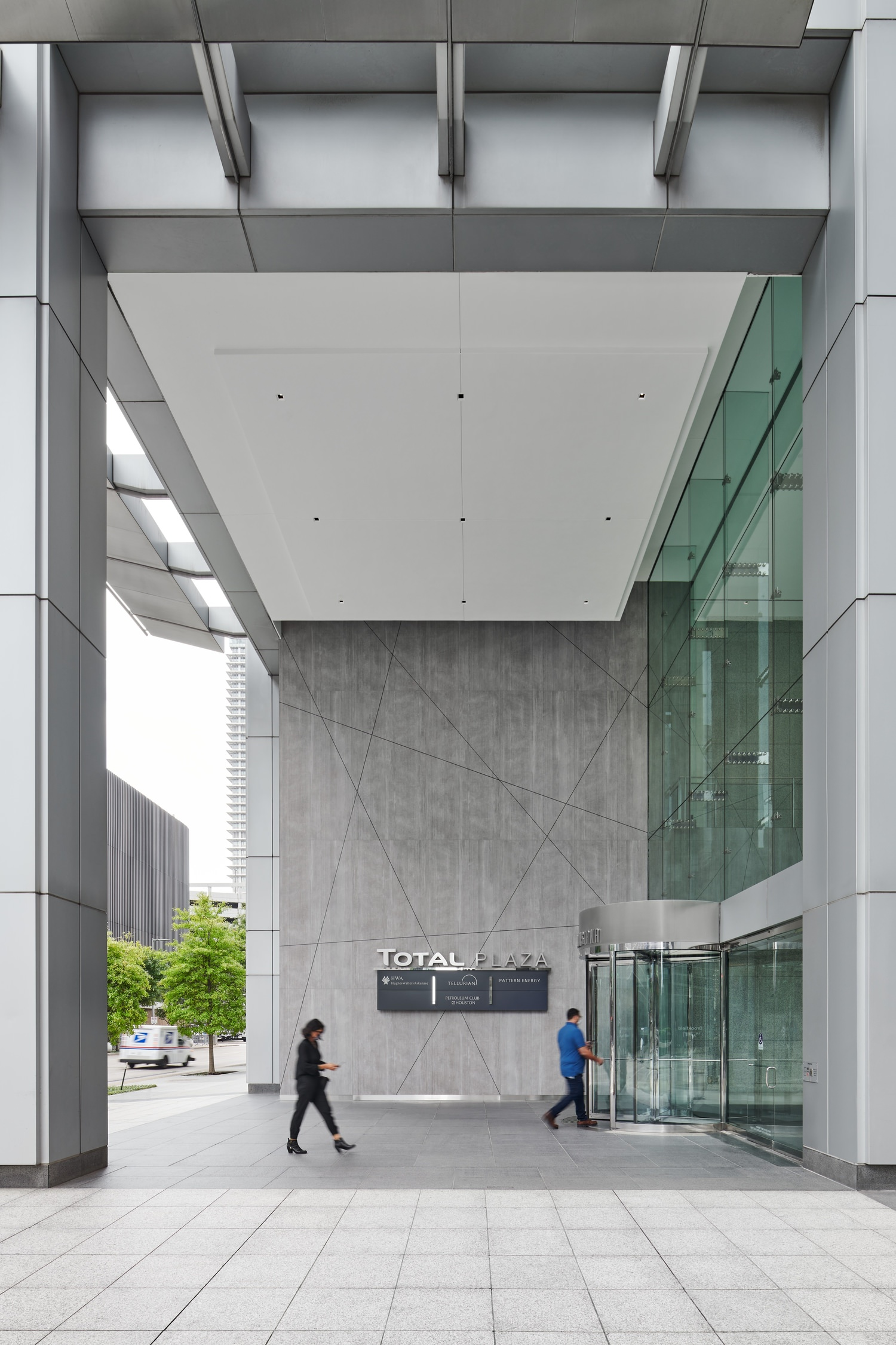 A group of people walking near the front of a large building with glass windows and walls.