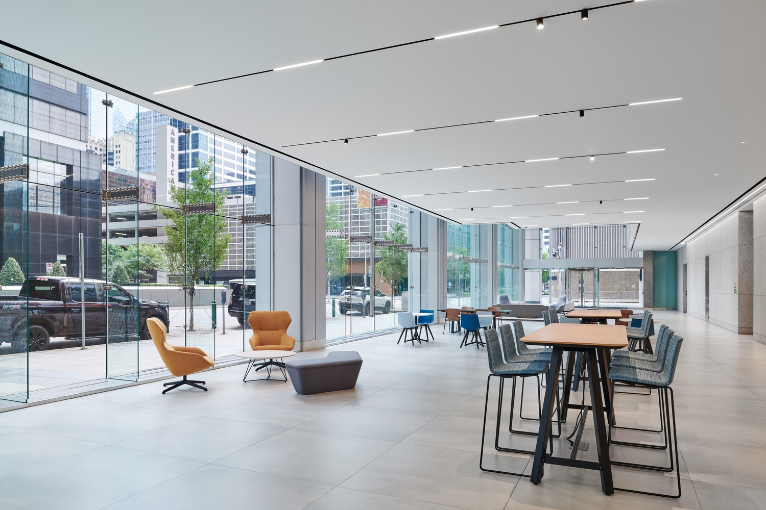The lobby of a large building that has some high tables with chairs and seating areas.