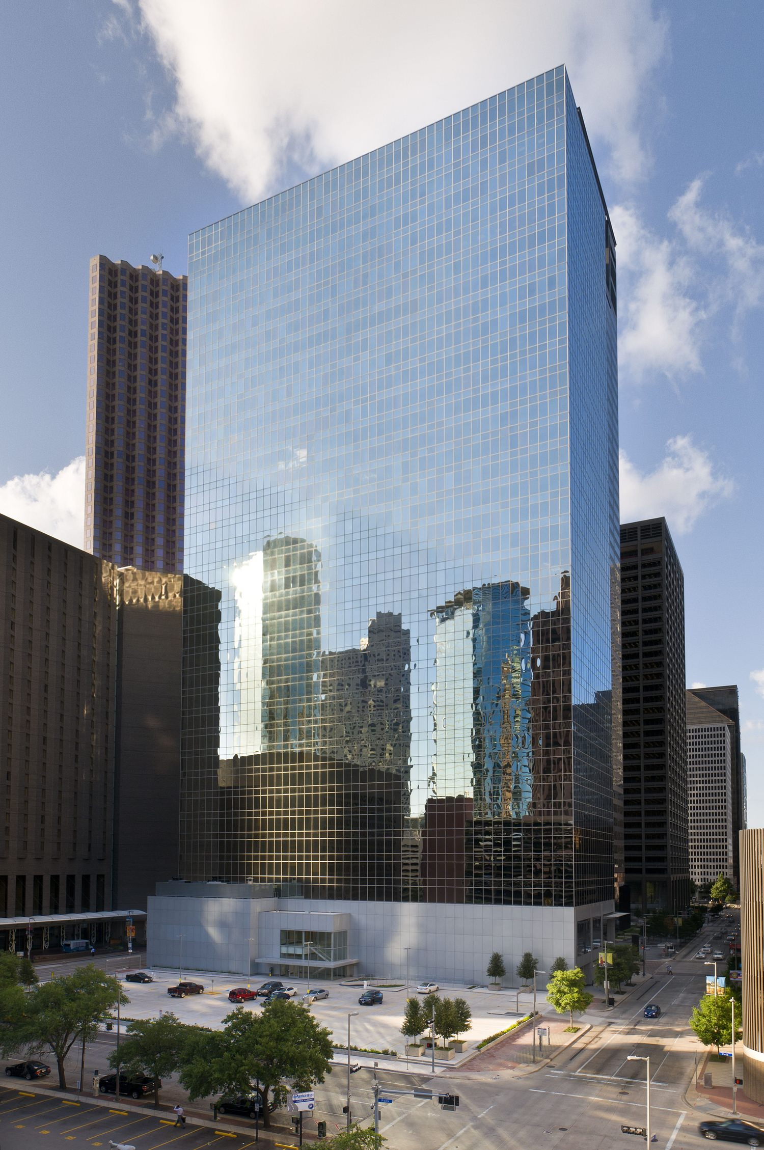A tall skyscraper that is full of glass windows on the oustide with a plaza next to it.