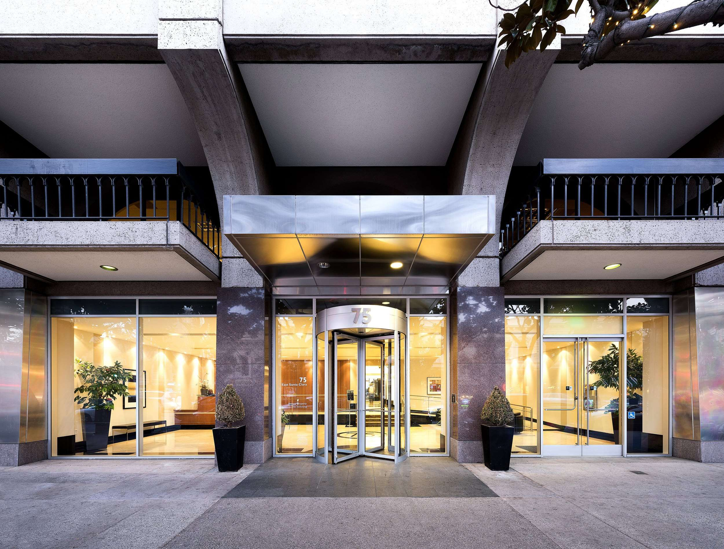 A large building that has a rotating door that goes into it as well as glass doors on either side of