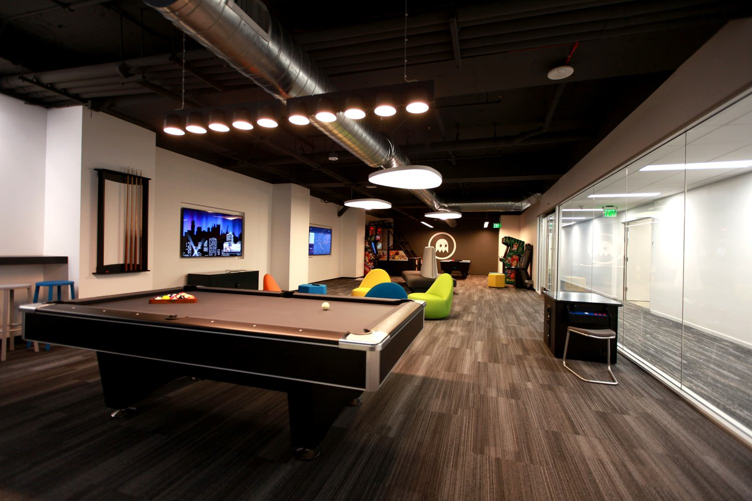 A recreational room with a pool table, arcade games, and lounge seating.