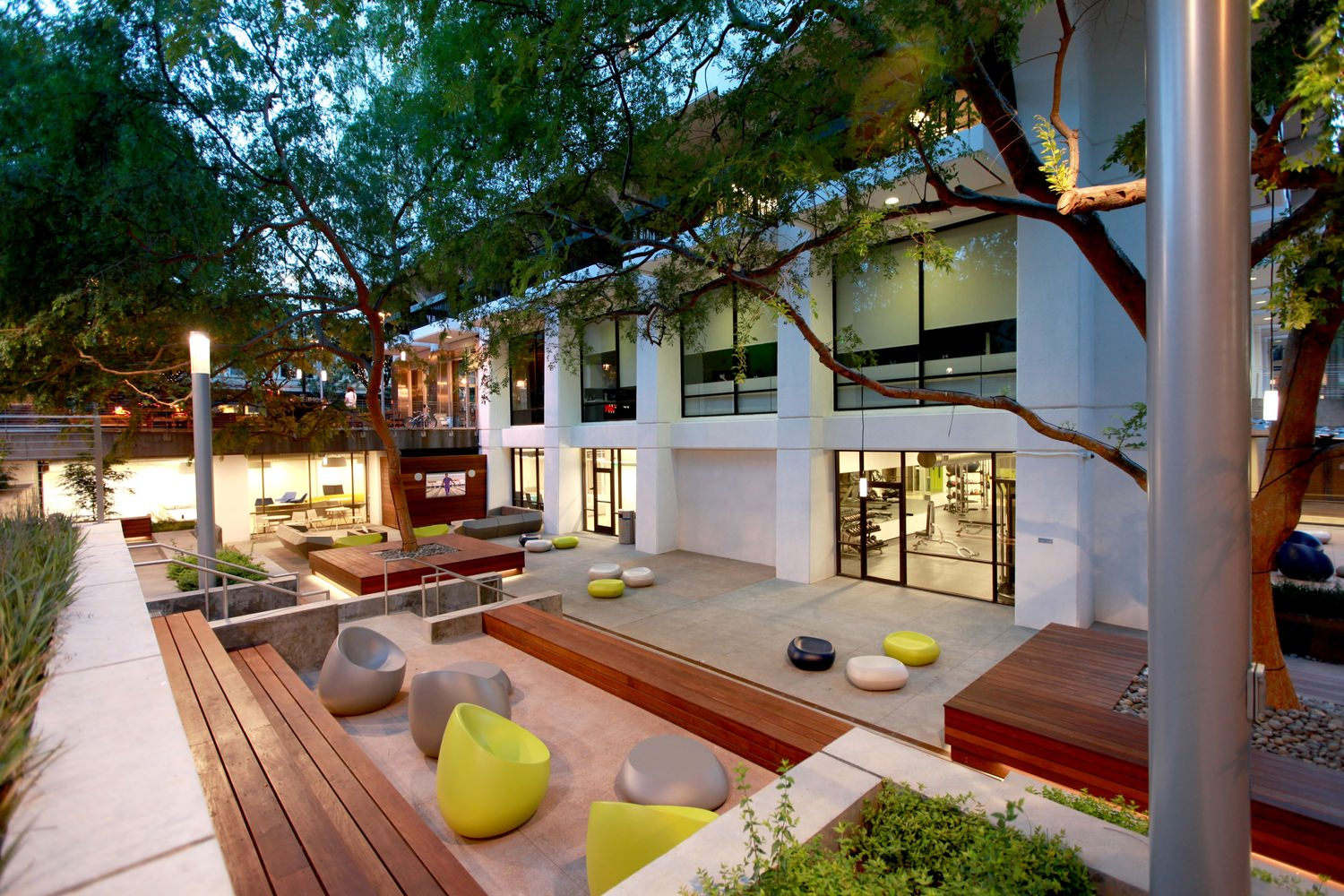 A white building with a courtyard that is full of trees and outdoor furniture along the area.
